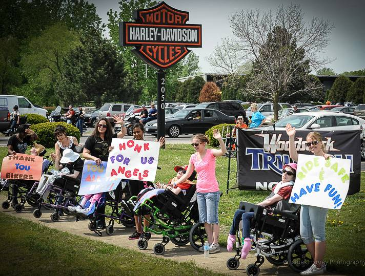 Fans wave with signs as the bikers pass during a previous Little Angels Pledge Run.