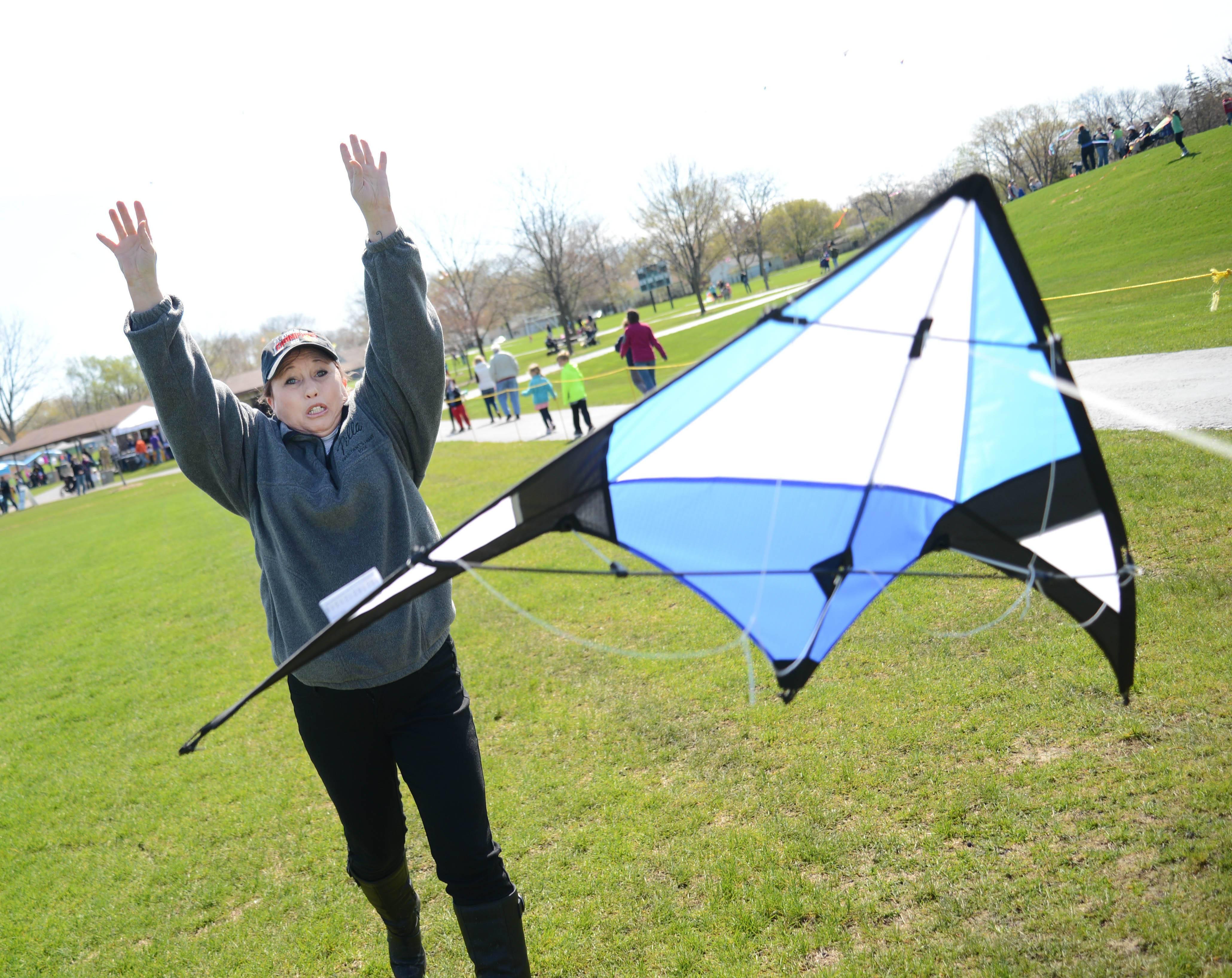 Christine Mirabella, of Aurora, releases a kite during the kite flying event at Graf Park in Wheaton on Saturday. More than 200 people took part. Prizes were given for the most unique kites.