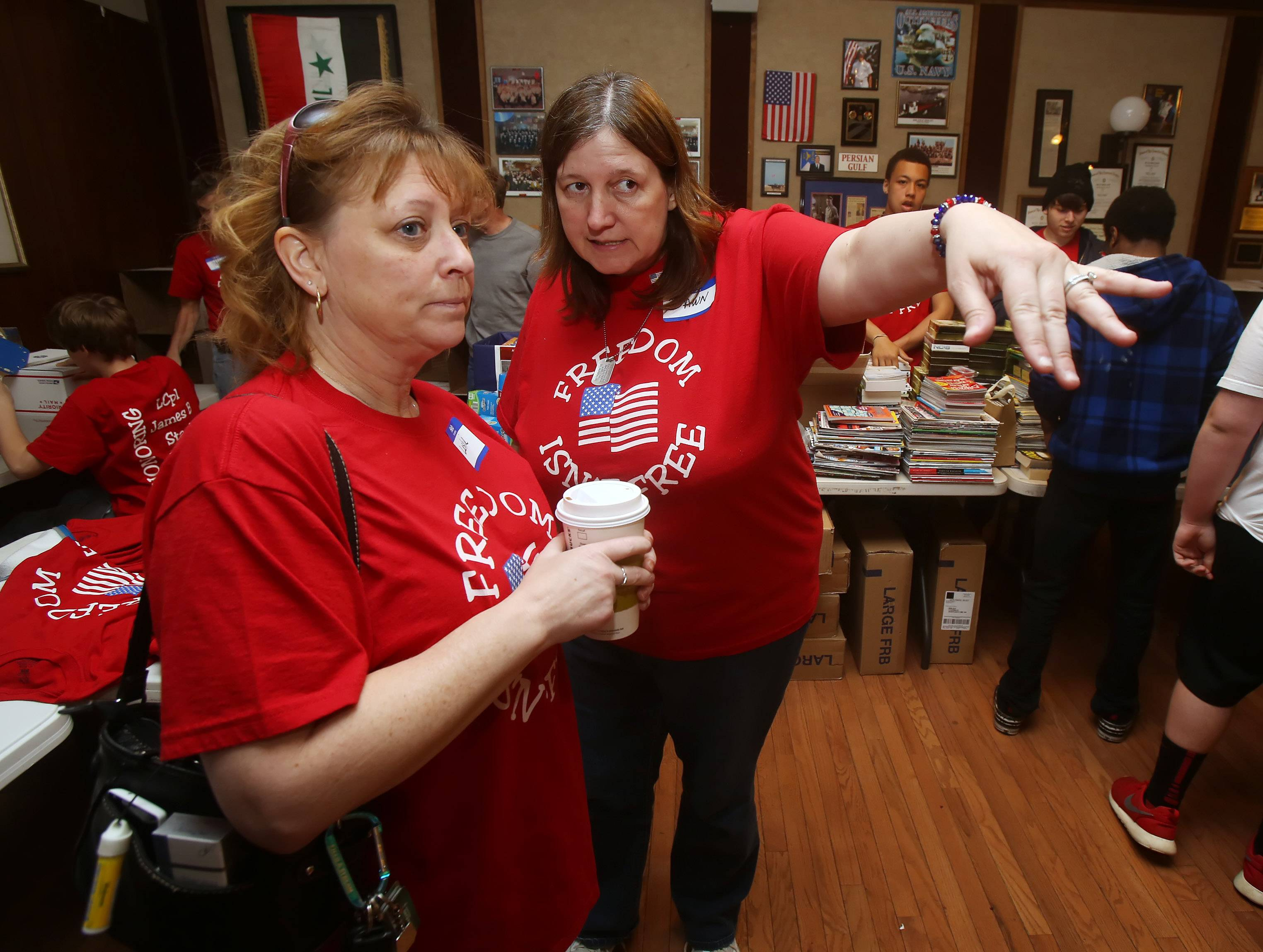 Dawn Hedrick, right, directs Leslie Anderson where help is needed as family and friends of fallen Arlington Heights Marine James Stack pack boxes of donations at the Arlington Heights American Legion Hall. The donations will be sent to troops in Afghanistan.