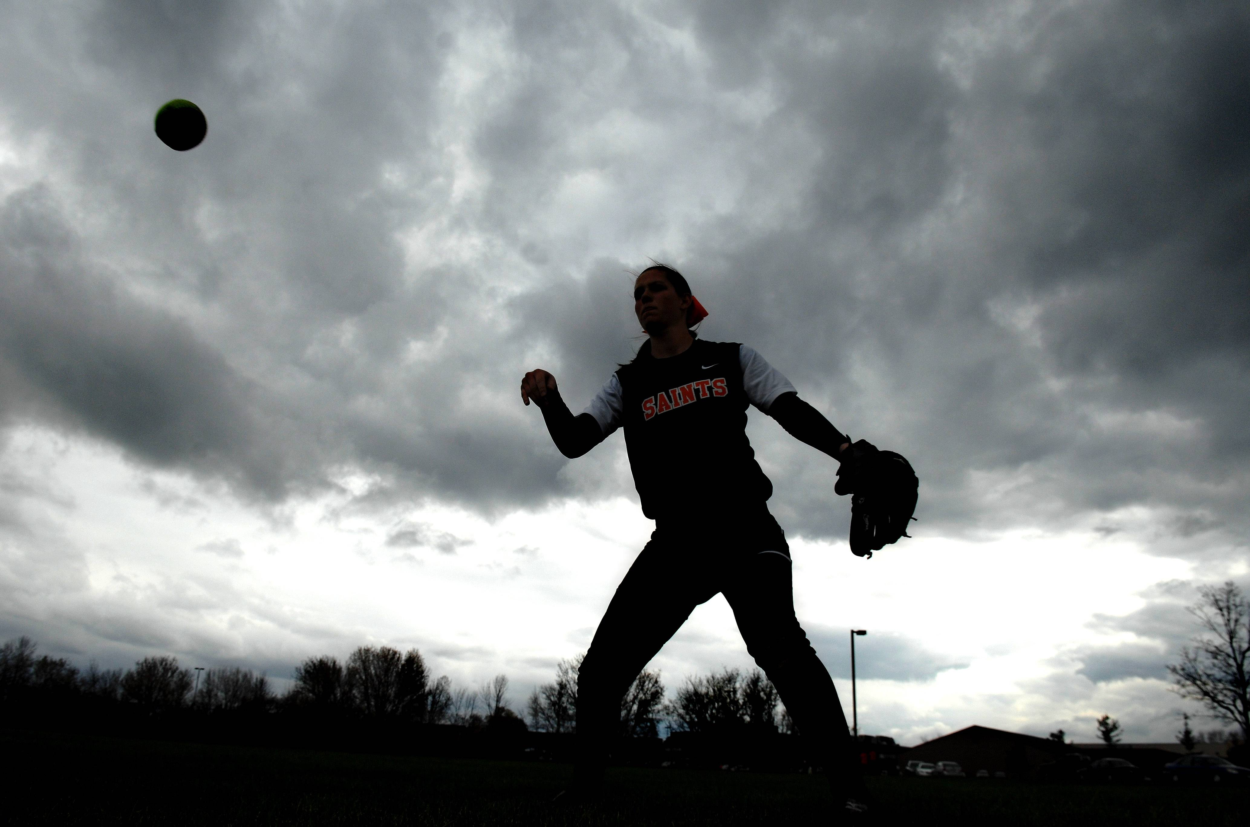 St. Charles East's Kelly Rinker warms up as storm clouds roll in before Tuesday's home game against rival St. Charles North.