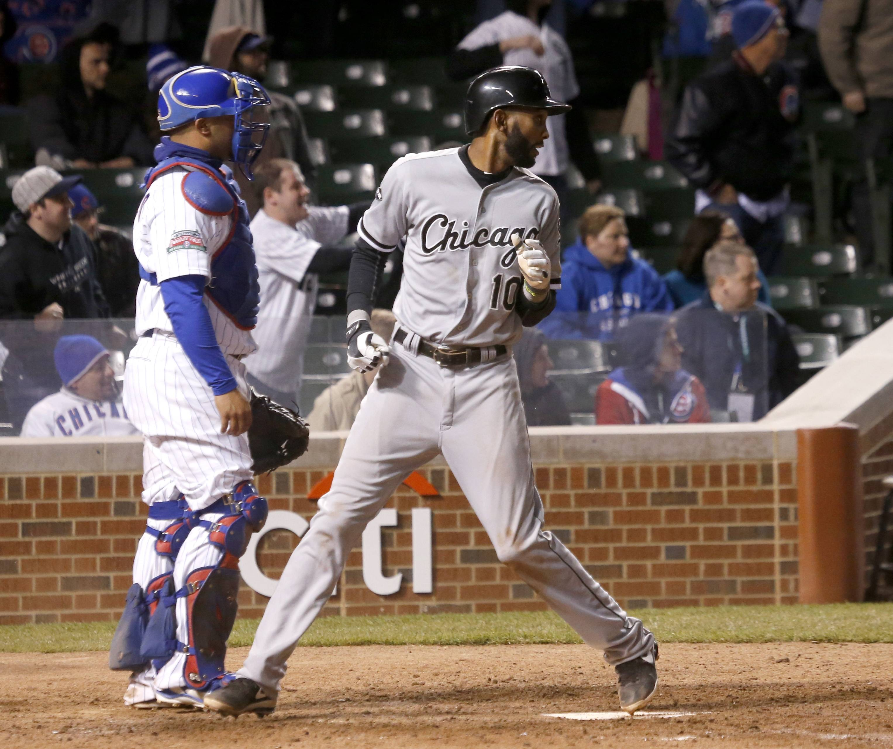Alexei Ramirez, right, of the White Sox looks back to the infield after scoring on a double by Marcus Semien during Monday's 12th inning at Wrigley Field.