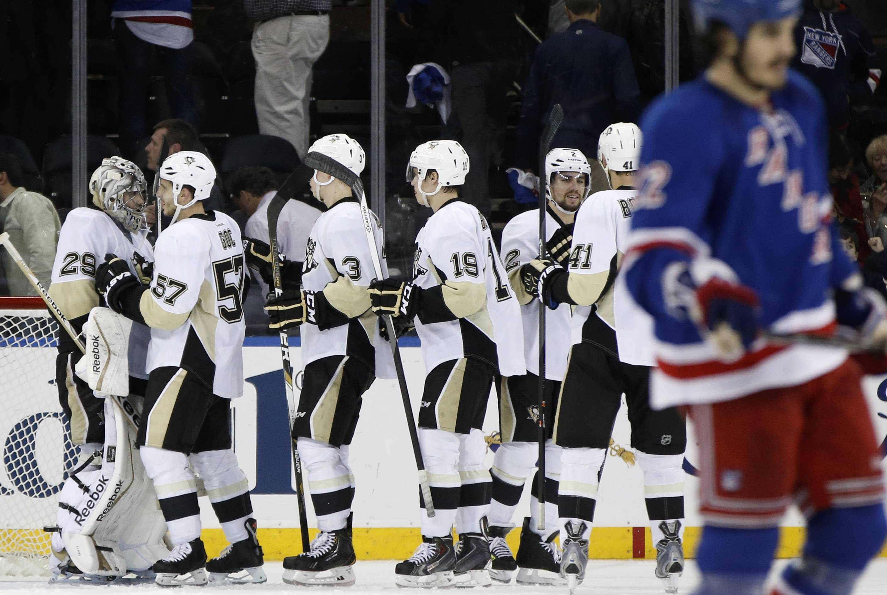 Teammates line up to congratulate Pittsburgh Penguins goalie Marc-Andre Fleury (29), far left, after the Penguins shut out the New York Rangers in their second-round NHL Stanley Cup hockey playoff game at Madison Square Garden in New York, Monday, May 5, 2014.  The Penguins lead the series 2-1. New York Rangers center Brian Boyle (22) leaves the ice, far right.