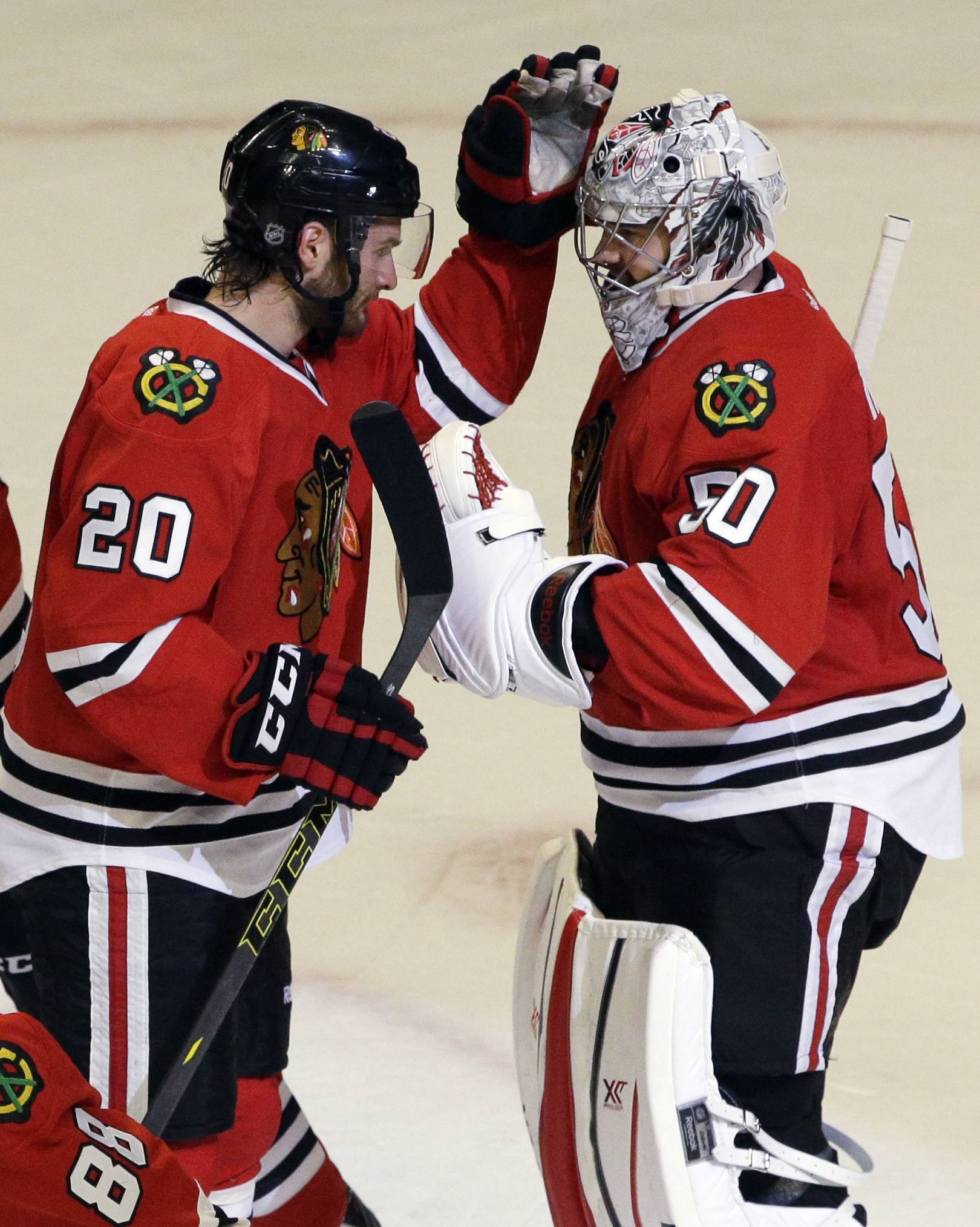 Blackhawks goalie Corey Crawford, right, celebrates with Brandon Saad after Sunday's Game 2 victory over the Wild at the United Center.