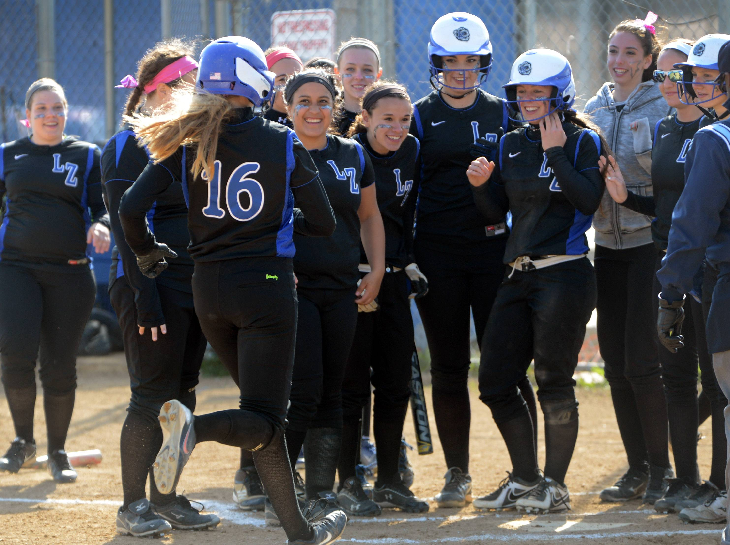 Lake Zurich's Amanda Guercio (16) is greeted at the plate after a first-inning home run against Zion-Benton in Lake Zurich.