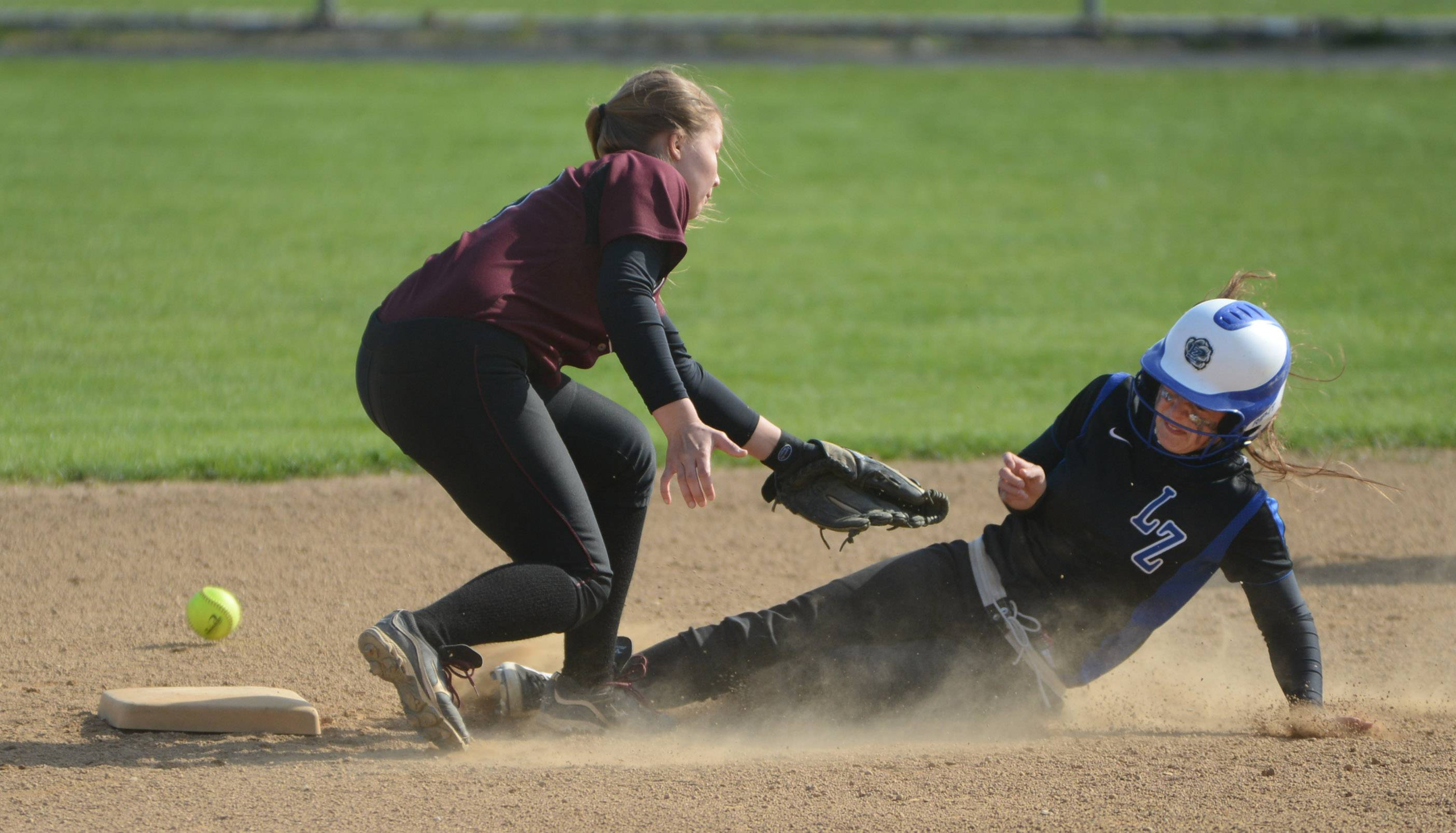 Lake Zurich's Maddie Minneci, right, slides safely into second base on an overthrow to Zion-Benton's Janie Torola Monday in Lake Zurich.