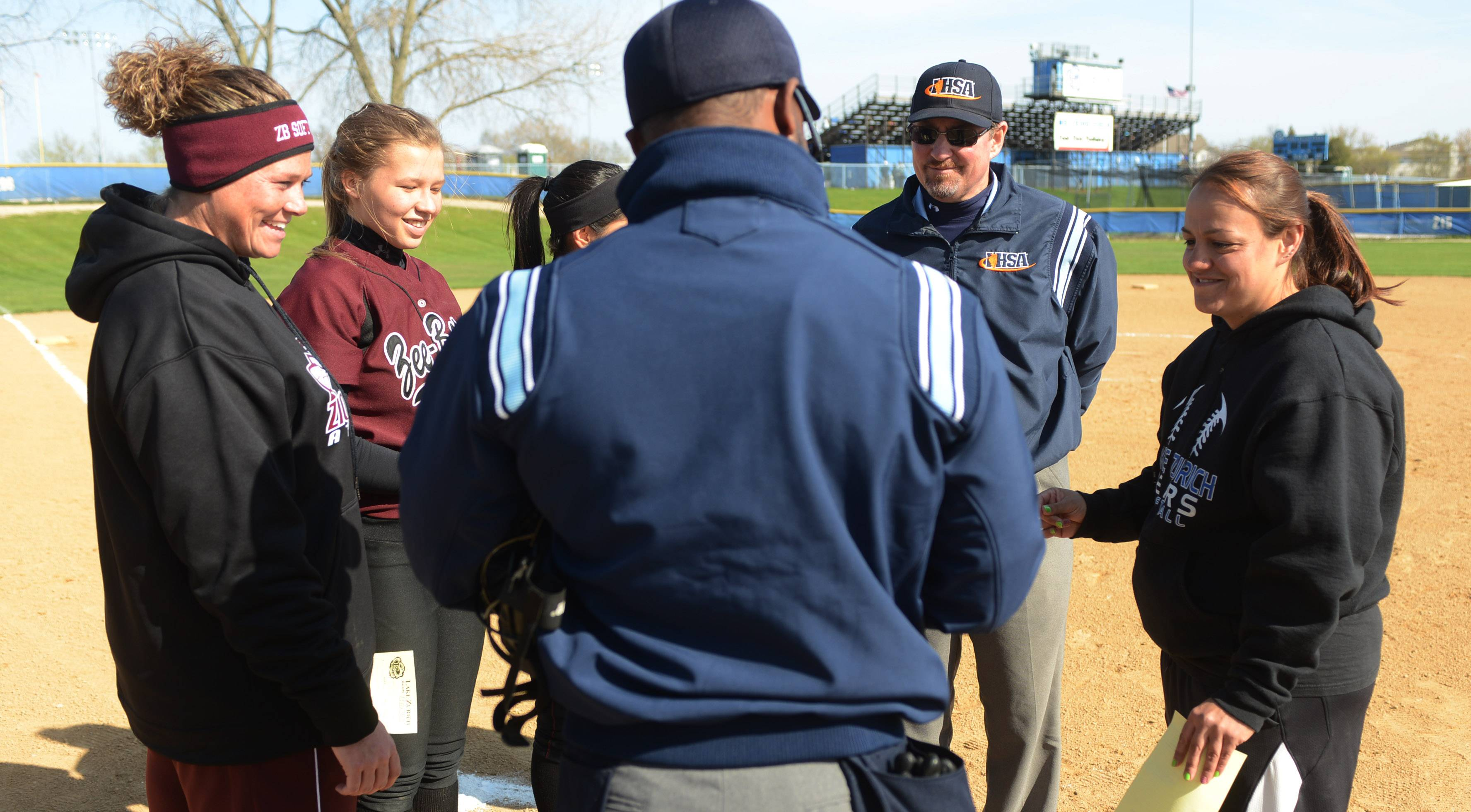 Zion-Benton coach Tina Meyer, left, and Lake Zurich coach Amanda Rodriguez, right, get instructions at the start of Monday's softball game in Lake Zurich. The two coaches played softball together at Round Lake High School.