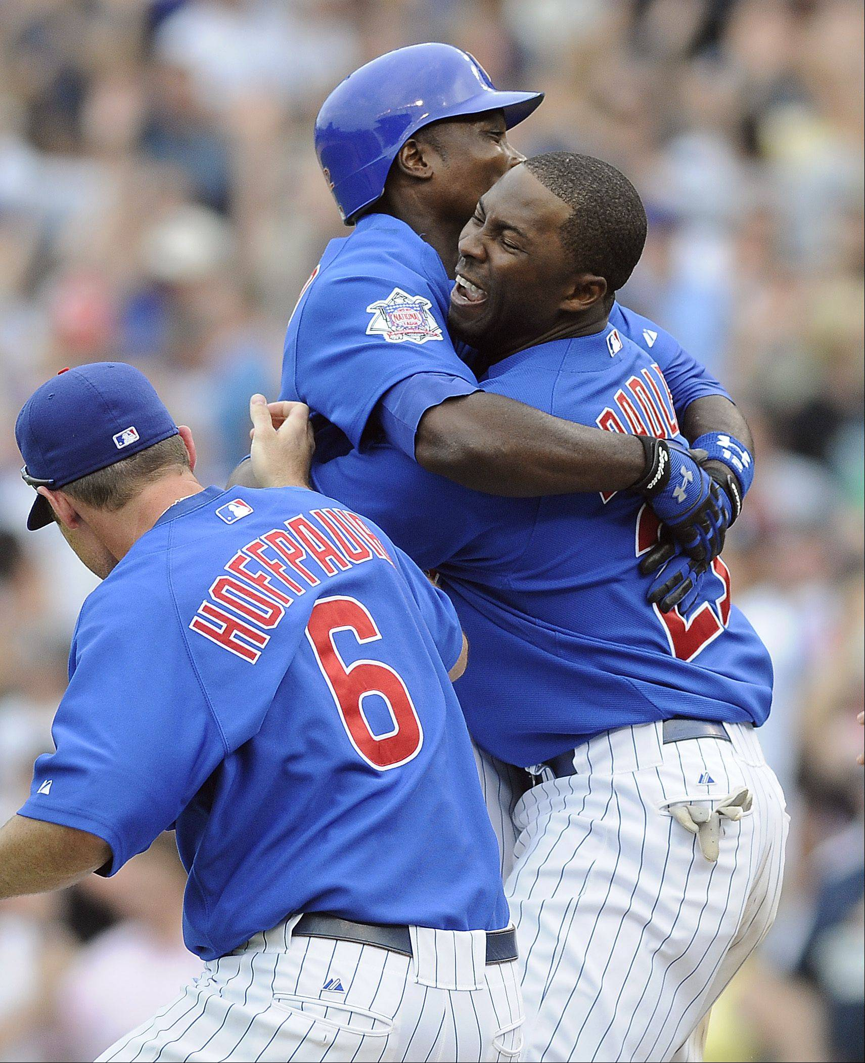 Chicago Cubs' Alfonso Soriano gets a hug from Milton Bradley, right, after Soriano's game-winning hit during the ninth inning of an interleague baseball game against the Chicago White Sox on Thursday, June 18, 2009, at Wrigley Field in Chicago. The Cubs won 6-5. At left is Micah Hoffpauir.