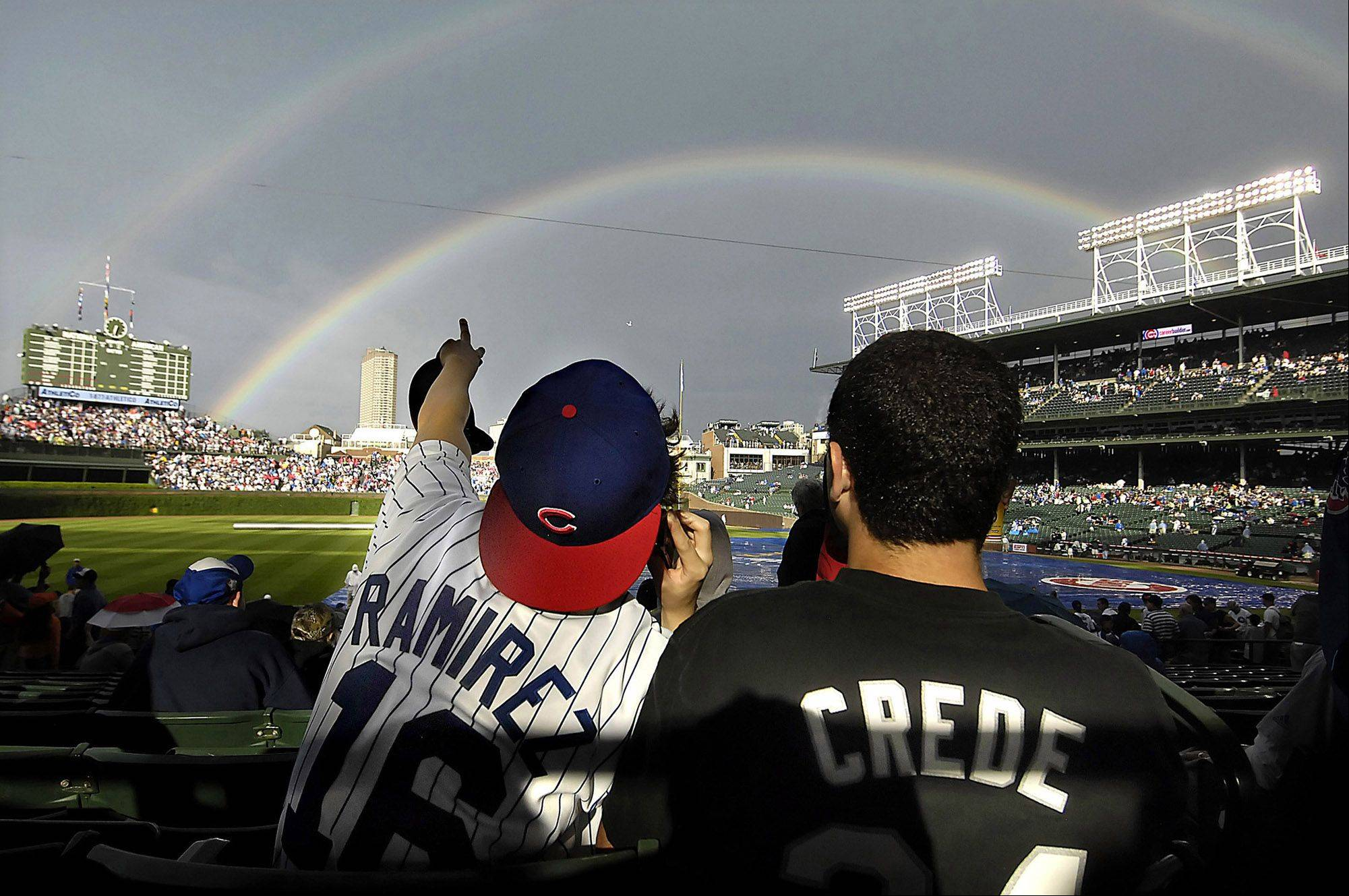 Cubs fan Michael Kiely and Sox fan Michael Gerb watch a double rainbow appear over Wrigley Field before the cross-town rivalry.