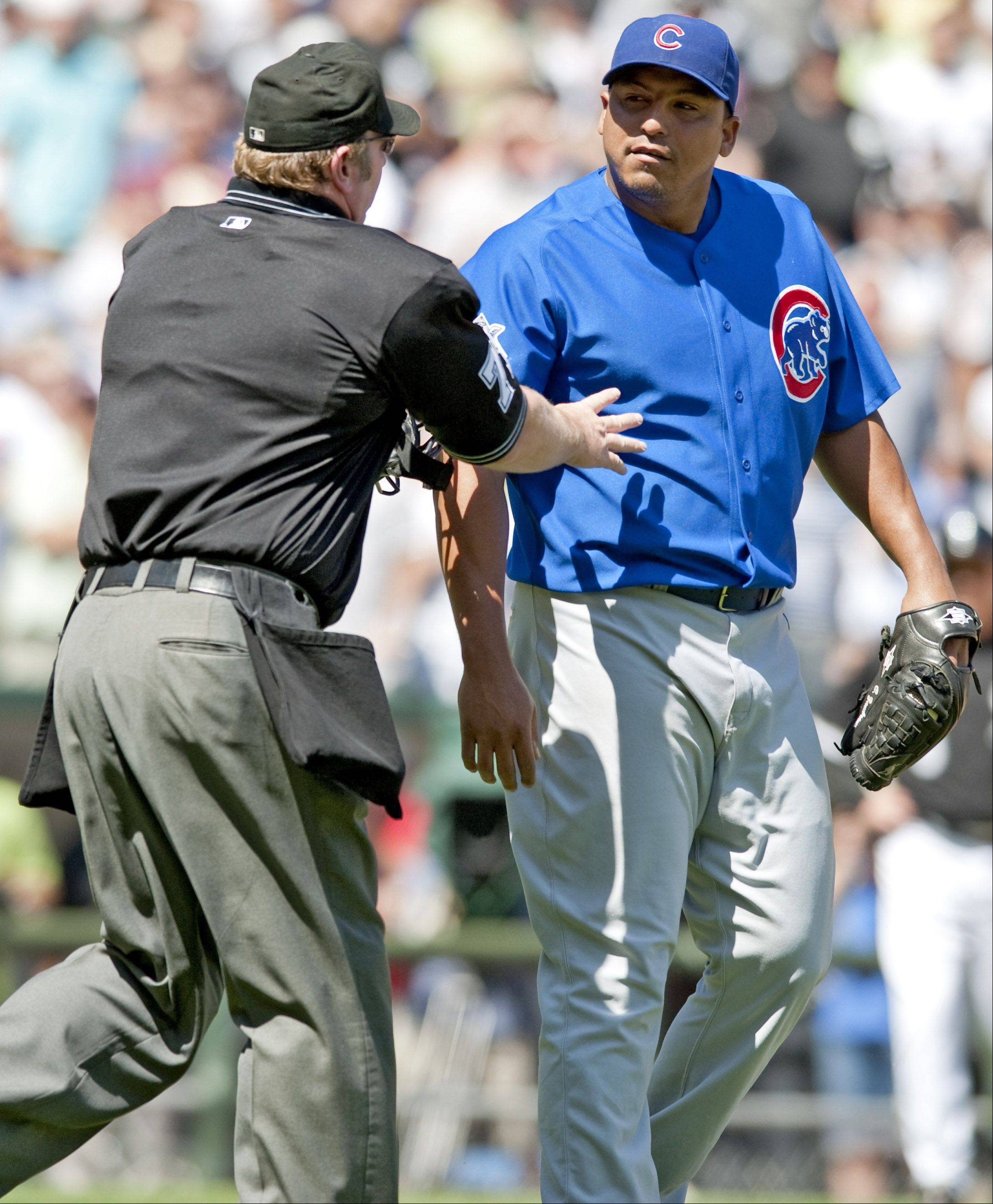 An official holds back Cubs pitcher Carlos Zambrano as he and Sox center fielder DeWayne Wise exchange words with one another after getting hit by a pitch during the sixth inning at U.S. Cellular Field on Sunday in Chicago.