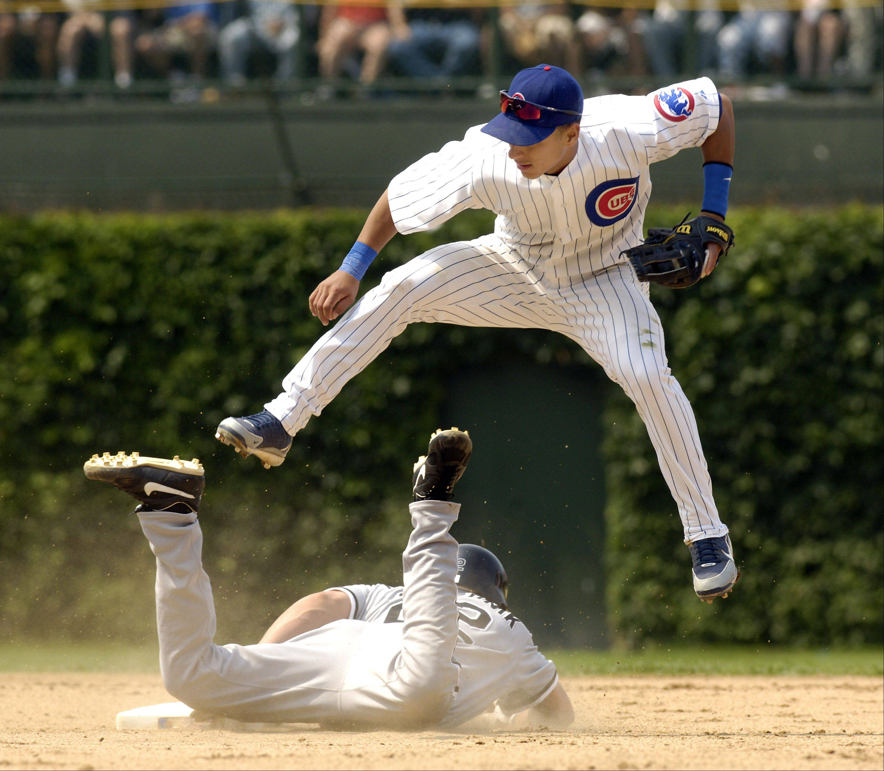 Ronny Cedeno goes up and over at secondbase as White Sox Scott Podsednik slides into the tagout on a steal.