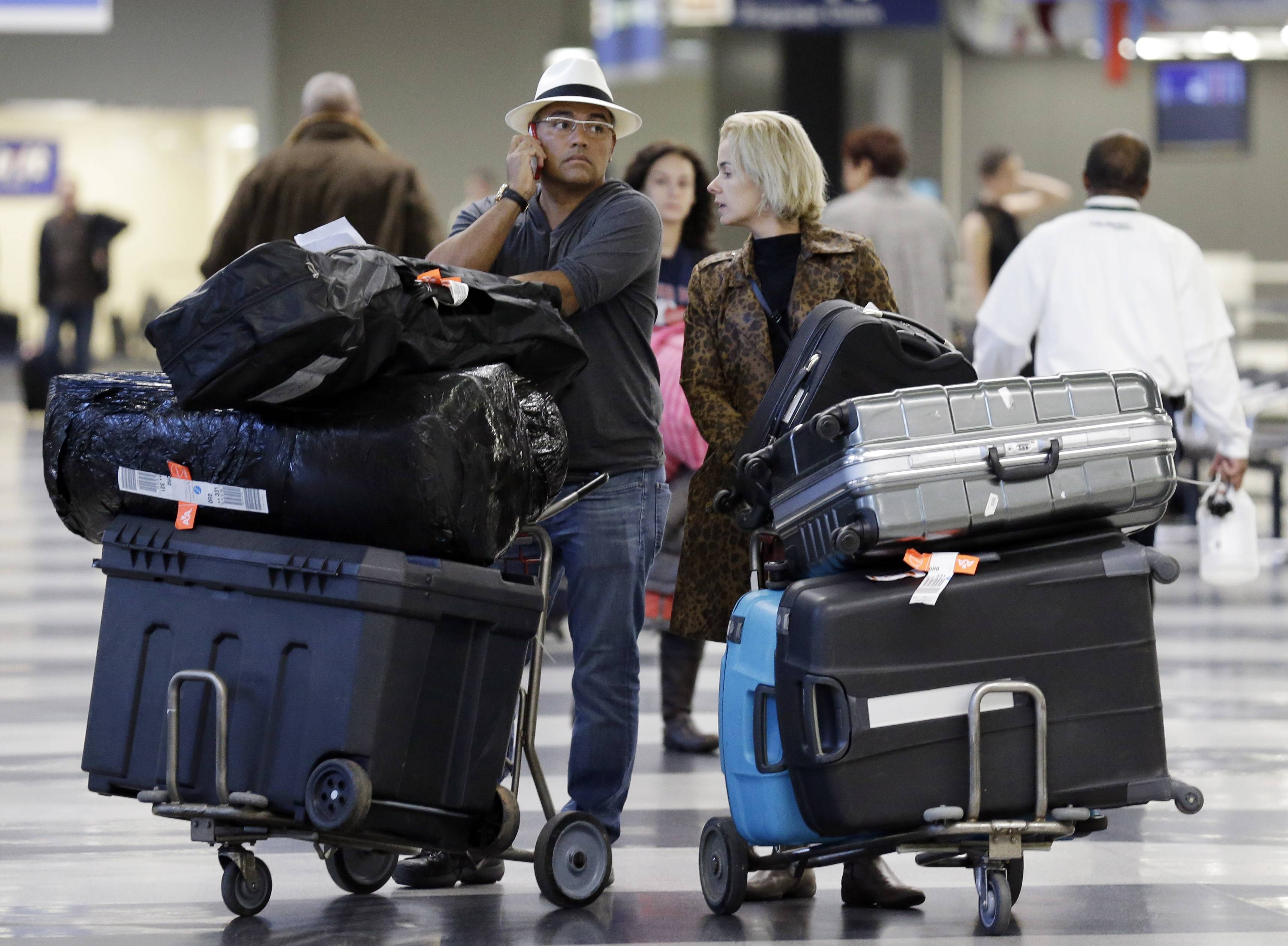 Travelers walk through terminal 3 baggage claim at O'Hare International airport in Chicago. U.S. airlines raised $3.35 billion from bag fees in 2013, down 4 percent from 2012. That's the biggest decline since fees to check a bag or two took off in 2008.