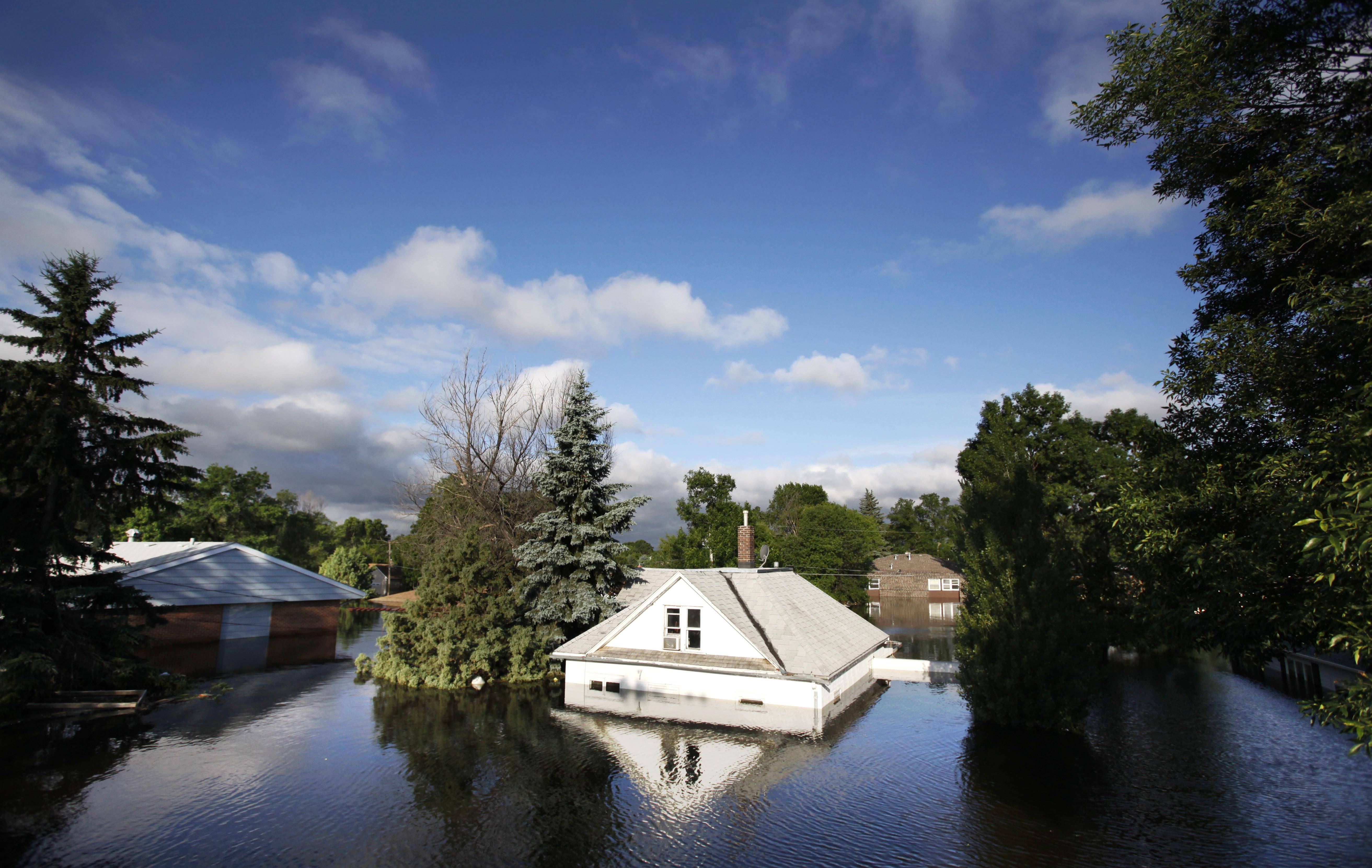 Floodwaters from the Souris River surround homes near Minot State University in Minot, N.D., June 27, 2011. Global warming is rapidly turning America the beautiful into America the stormy, sneezy and dangerous, according to the National Climate Assessment report released Tuesday.