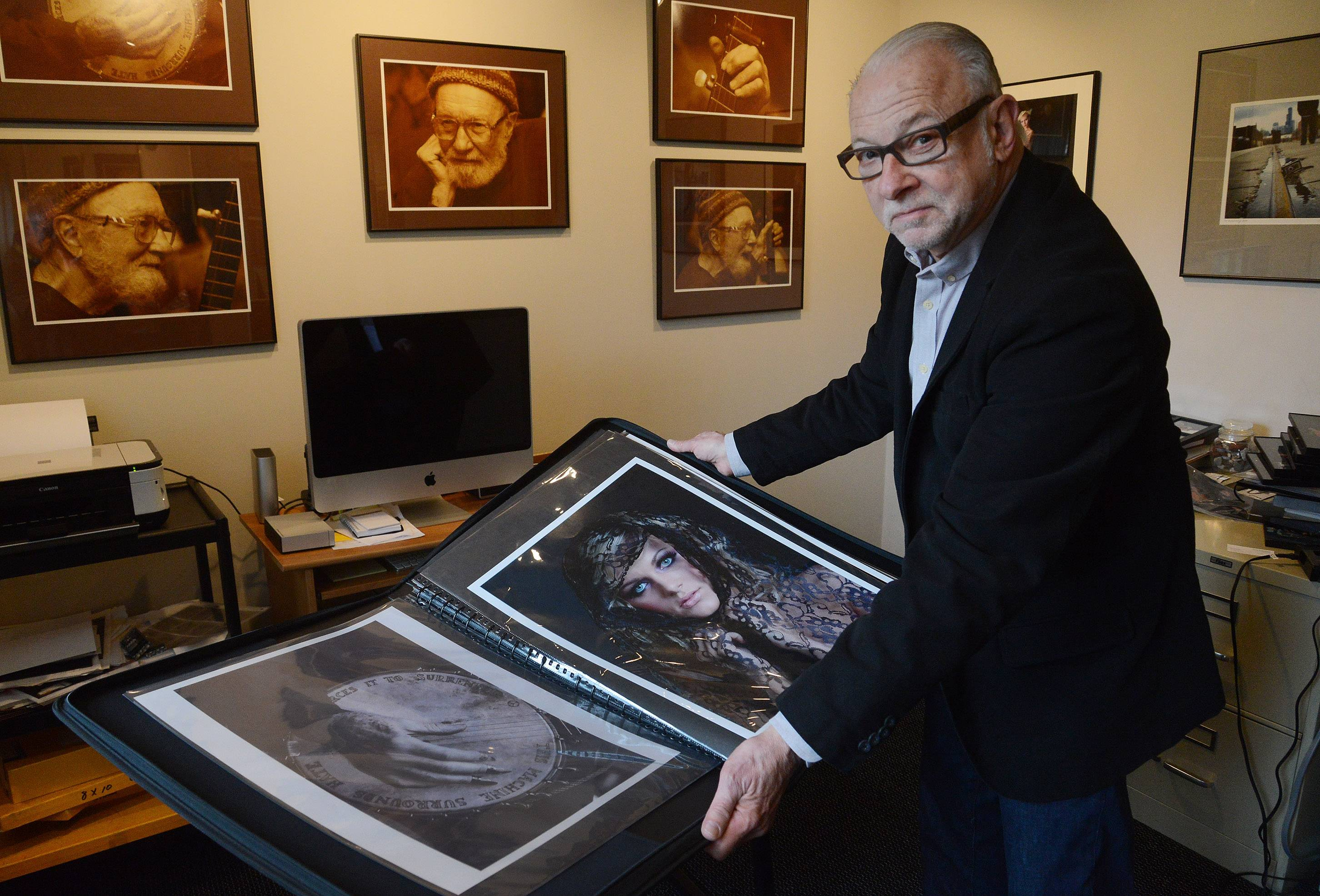 Deerfield photographer Bruce Mondschain with his work. The ones on the wall are sepia versions of his Pete Seeger photos.