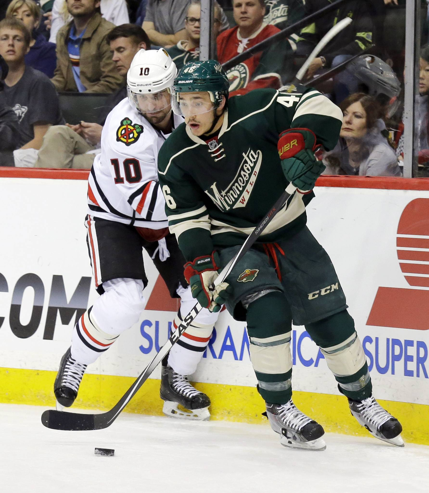 Minnesota Wild defenseman Jared Spurgeon (46) and Chicago Blackhawks left wing Patrick Sharp (10) chase the puck during the second period of Game 3 of an NHL hockey second-round playoff series in St. Paul, Minn., Tuesday, May 6, 2014. (AP Photo/Ann Heisenfelt)