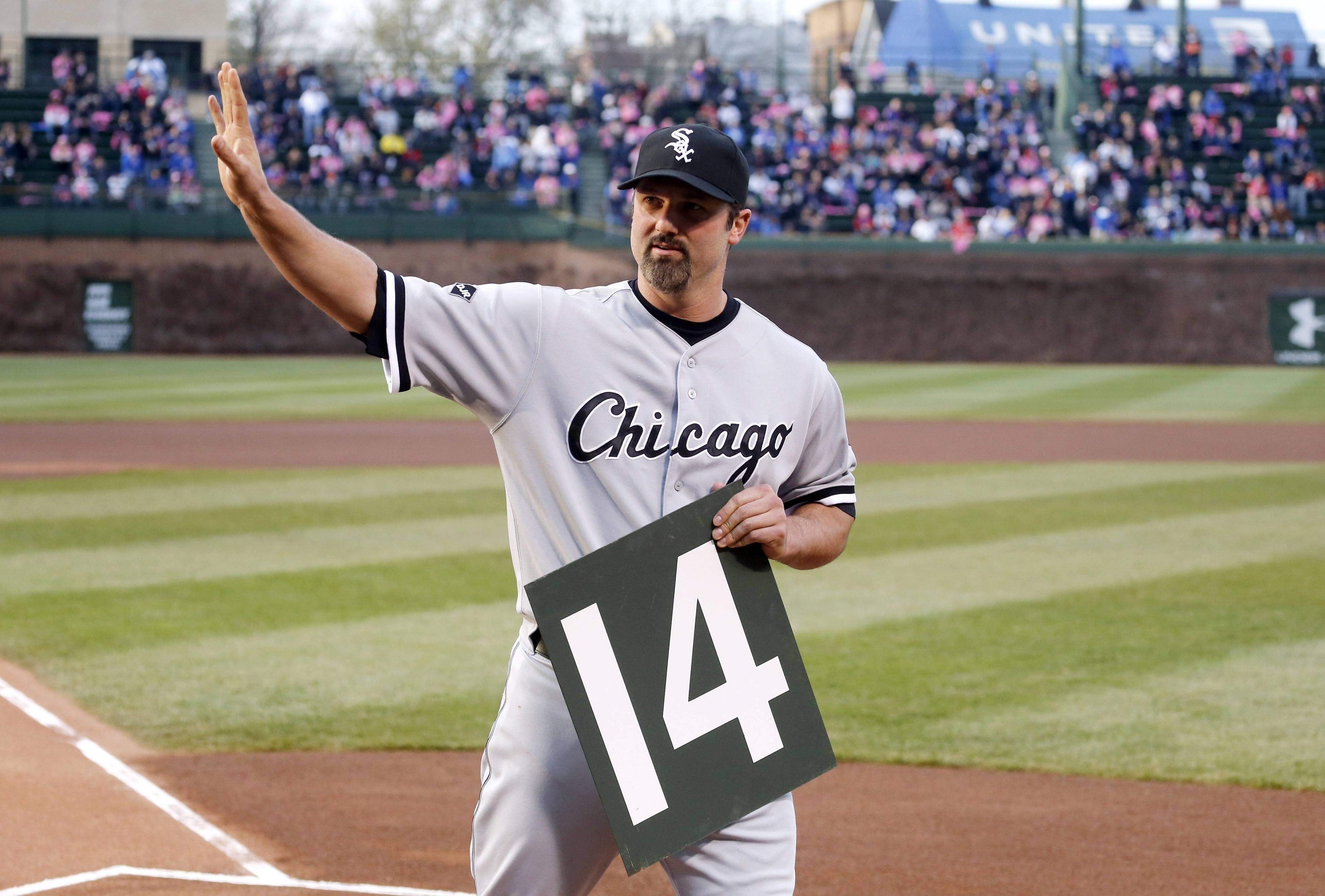 Chicago White Sox's Paul Konerko waves to the crowd after receiving a retirement gift from Chicago Cubs starting pitcher Jeff Samardzija of his number from the Wrigley Field scoreboard before a baseball game between the two teams Tuesday, May 6, 2014, in Chicago. (AP Photo/Charles Rex Arbogast)