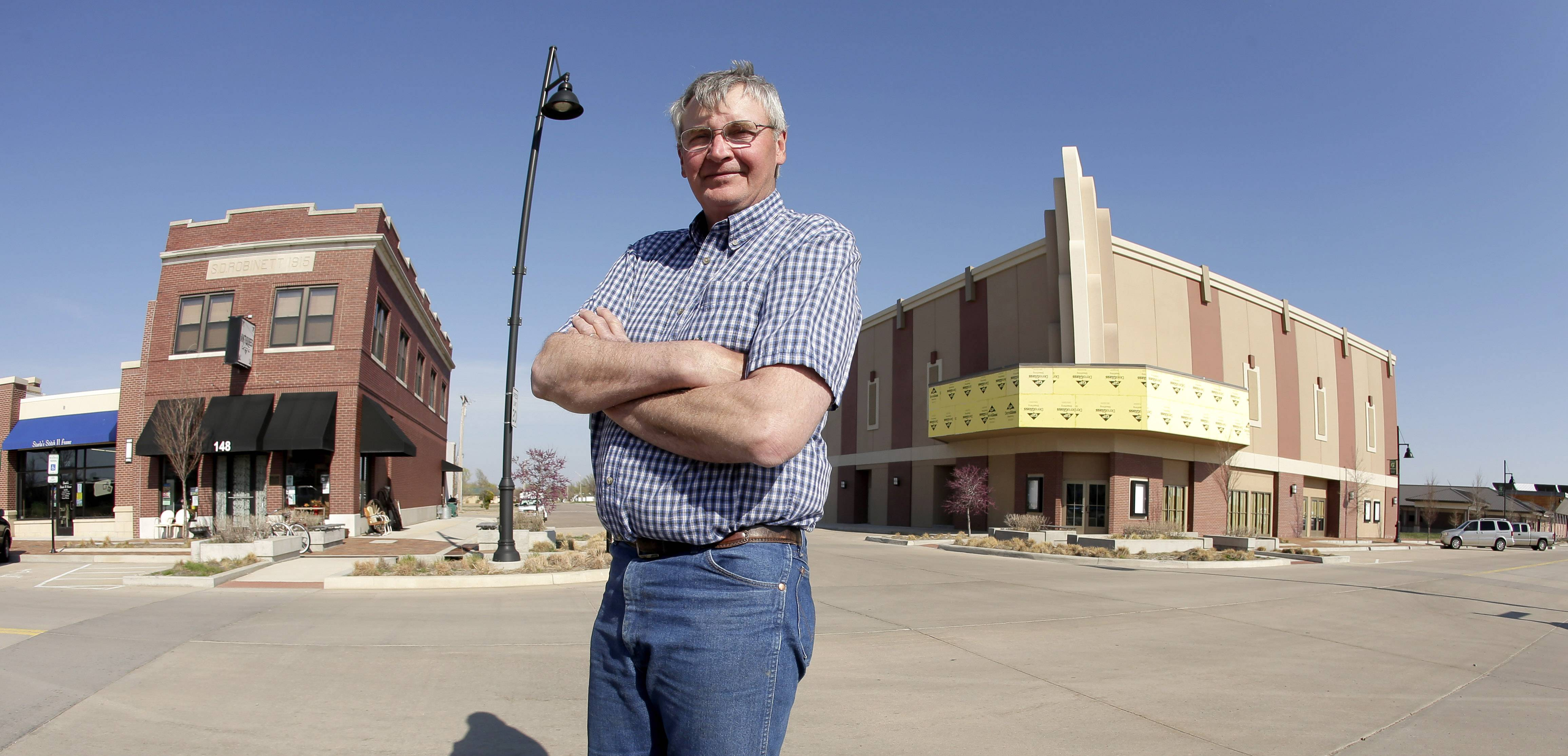 Mayor Bob Dixson stands with a soon-to-be completed community theater, at right, and the only downtown building to survive a massive tornado in Greensburg, Kan. Seven years after an EF-5 tornado destroyed most of the community of 1,500, Dixson believes most of the town's current 850 residents are ready to move on and deal with the same sort of problems that plague most rural communities.