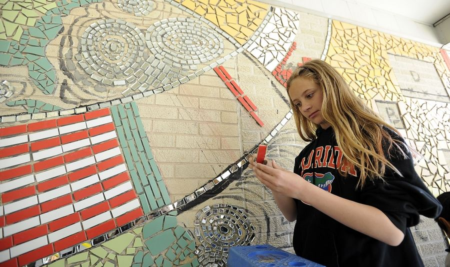 Sarah Teehan, 12, helps install a mural Tuesday designed to bridge cultural differences at Jane Addams Elementary School in Palatine.
