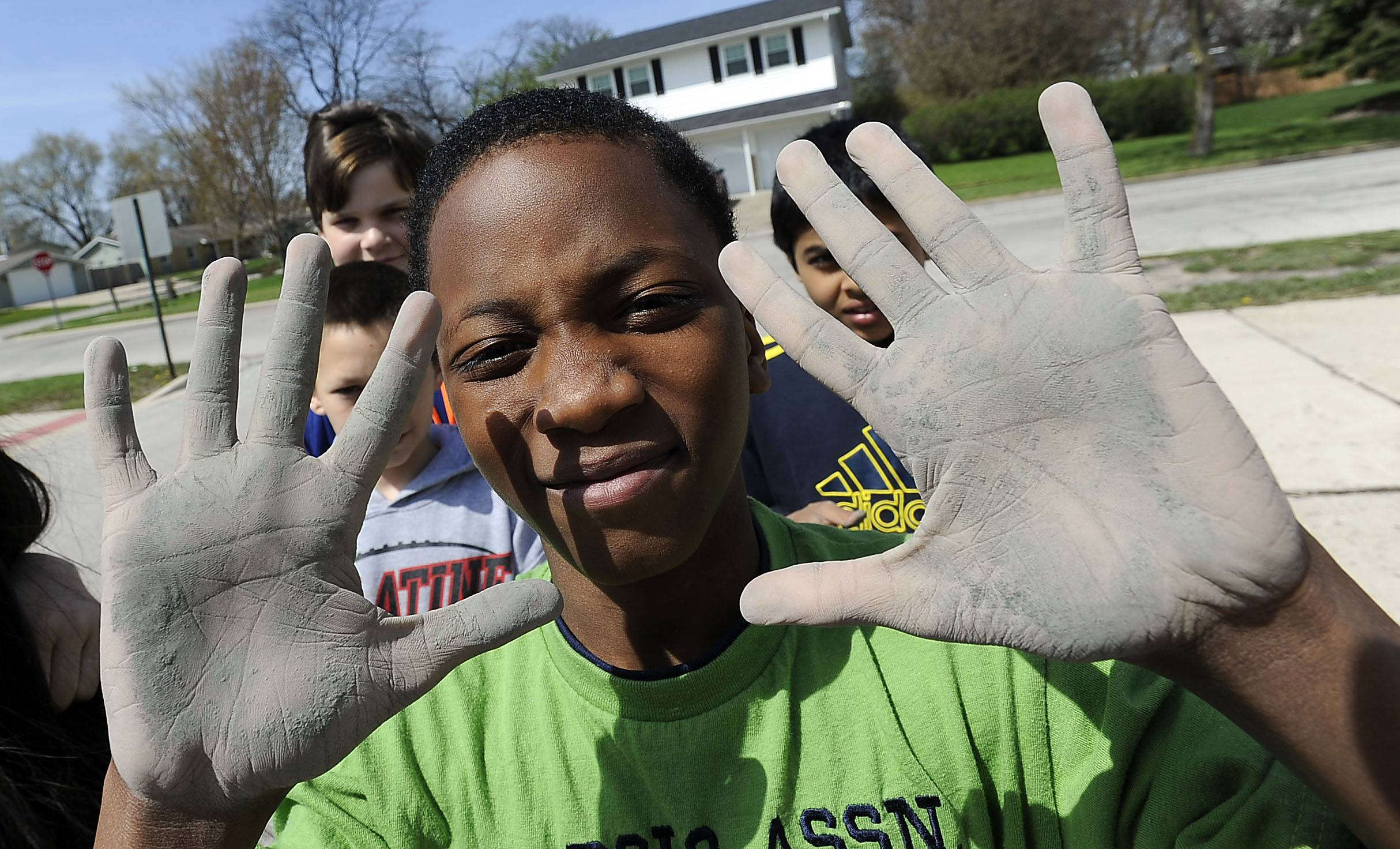 Avion Walker, 12, shows off his dirty hands Tuesday after working on the mural being created on the side of Jane Addams Elementary School in Palatine.
