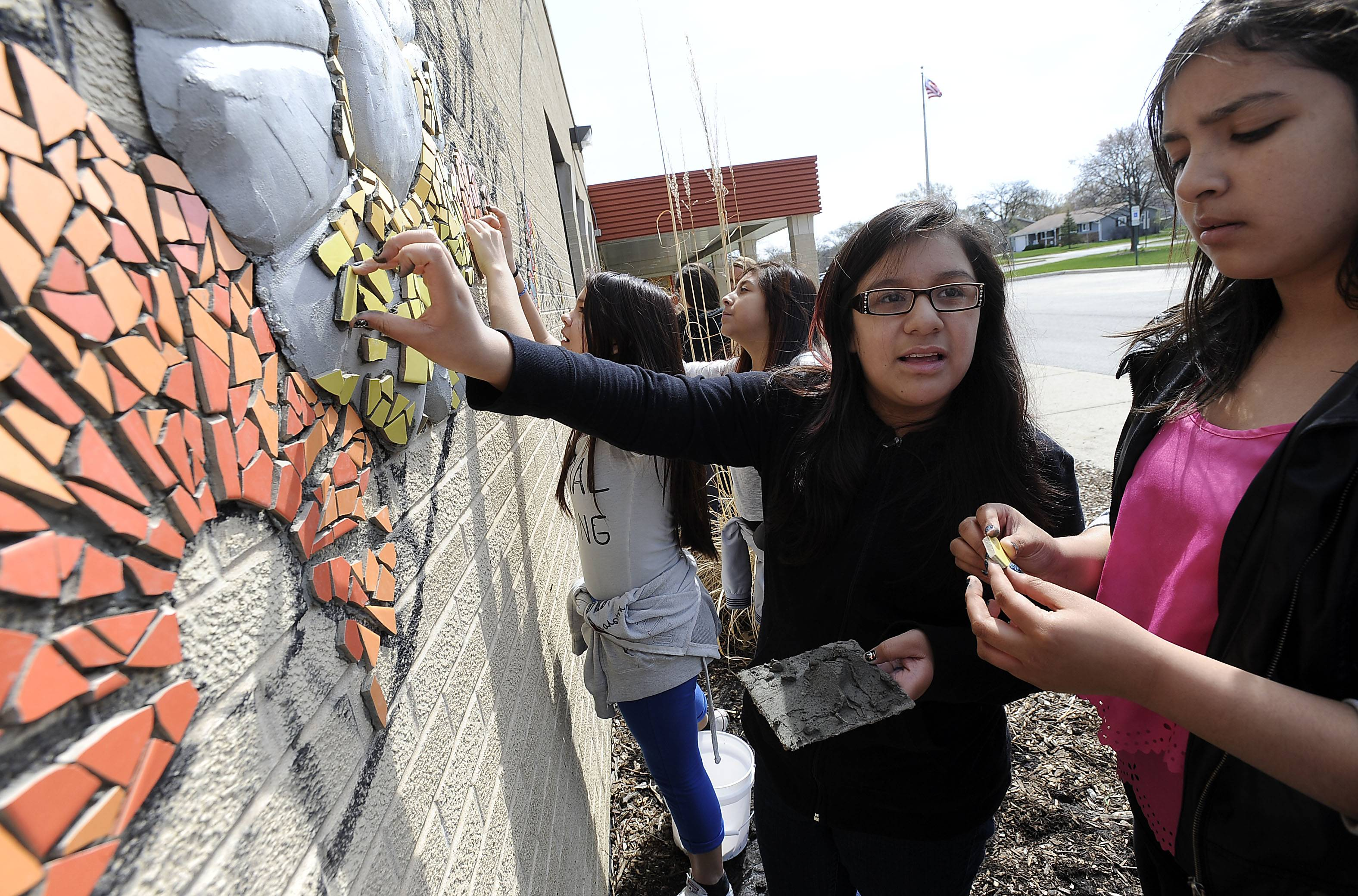 Gali Lopez and Litzy Gorostieta, both 12, lend a hand to the three-dimensional mural being created on the side of Jane Addams Elementary School in Palatine.