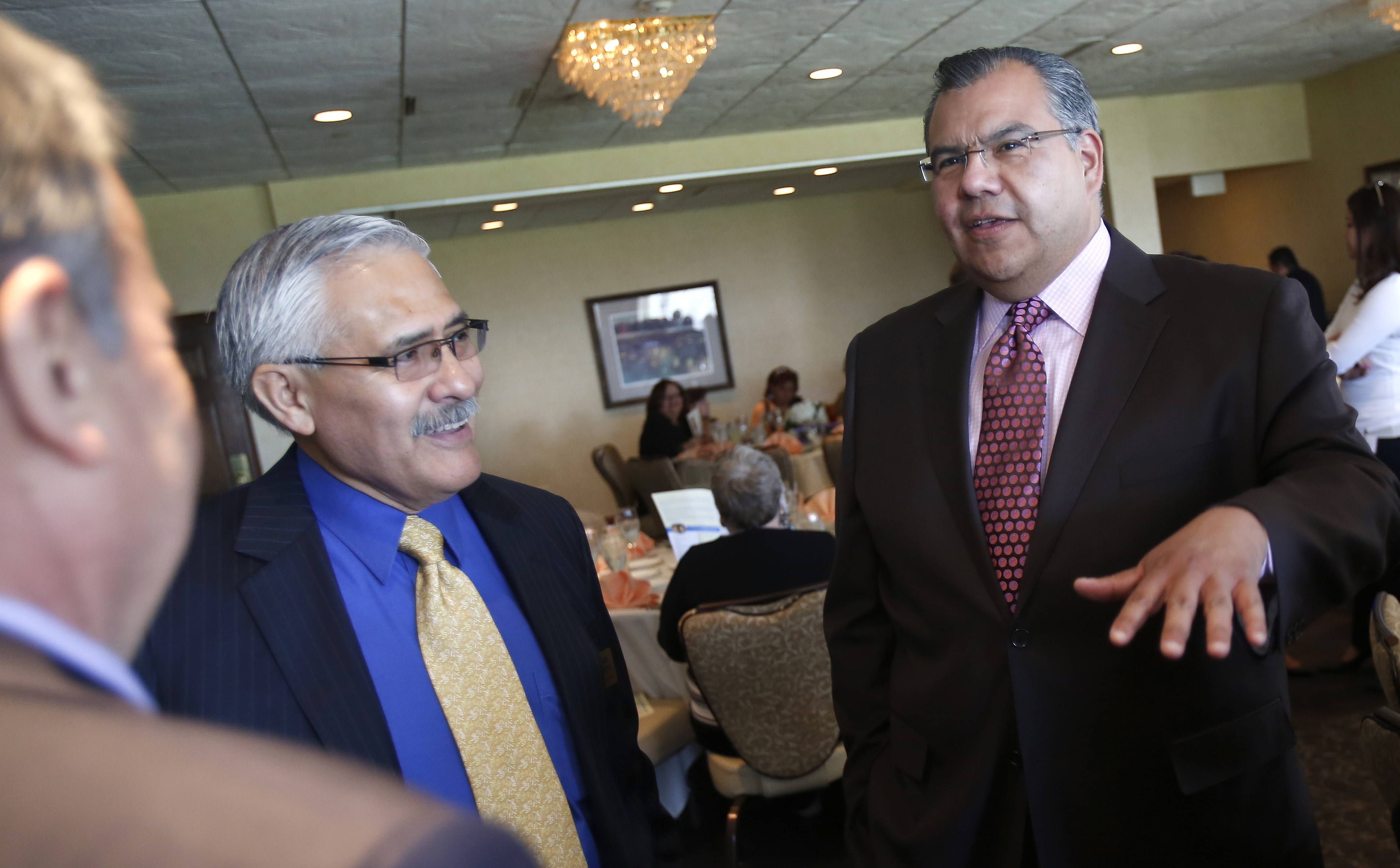 Martin Castro, chairman of the U.S. Commission on Civil Rights, talks to Jamie Garcia, left, executive director of Centro de Informacion, Tuesday at the annual Community Day luncheon benefiting Centro de Informacion at Elgin Country Club.