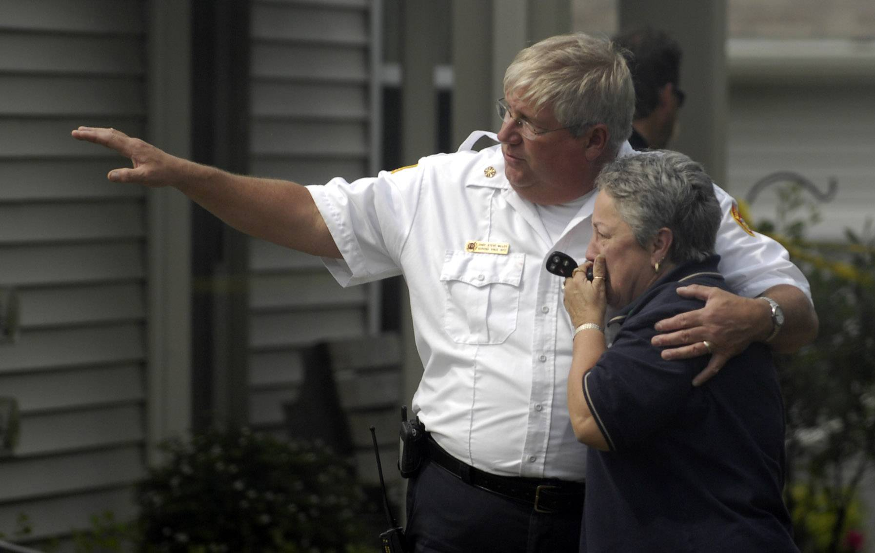 North Aurora Fire Protection District Chief Steve Miller consoles a resident after her Sugar Grove home burned in a 2009 fire. Miller retired April 30 after 42 years with the district.