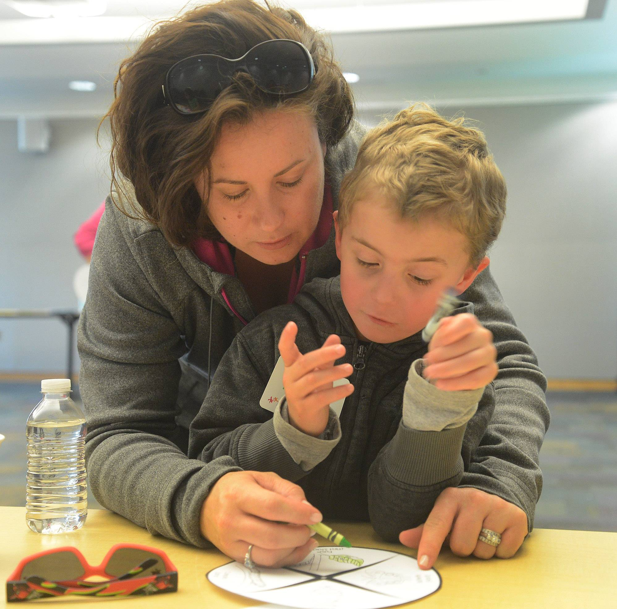 Christina Fejes of Lincolnshire helps her son, Henry, color a butterfly, during the Vernon Area Public Library's Preschool Science Detectives program Tuesday.