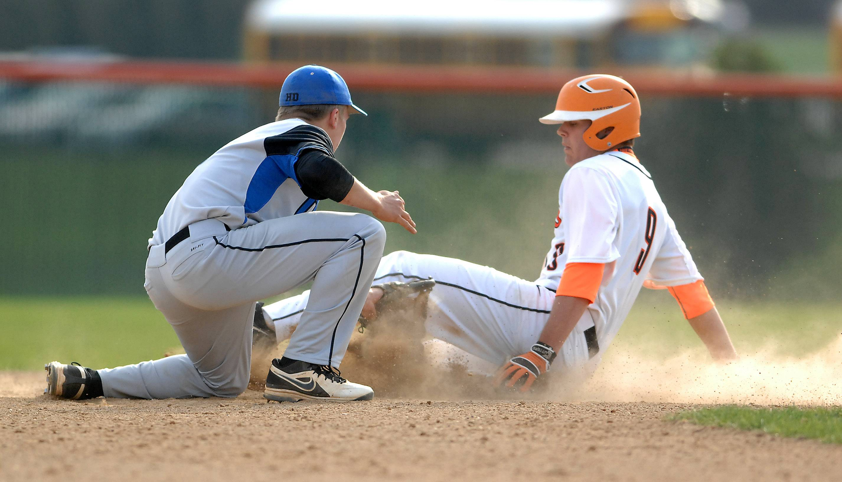 St. Charles East's Erik Anderson (9) slides safely into second with a steal after the ball got under the glove of St. Charles North's Riley Coomes (16) during Tuesday's game at St. Charles East.