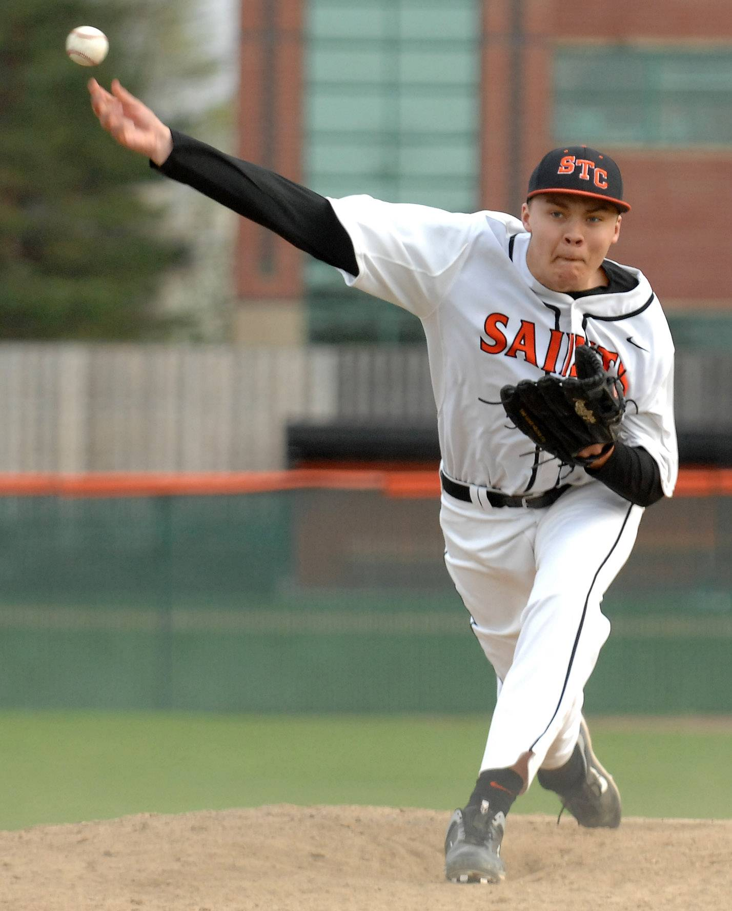 St. Charles East's Michael Vyzral (14) makes a pitch in relief that gets the Saints out of a bases loaded jam against St. Charles North during Tuesday's game at St. Charles East.