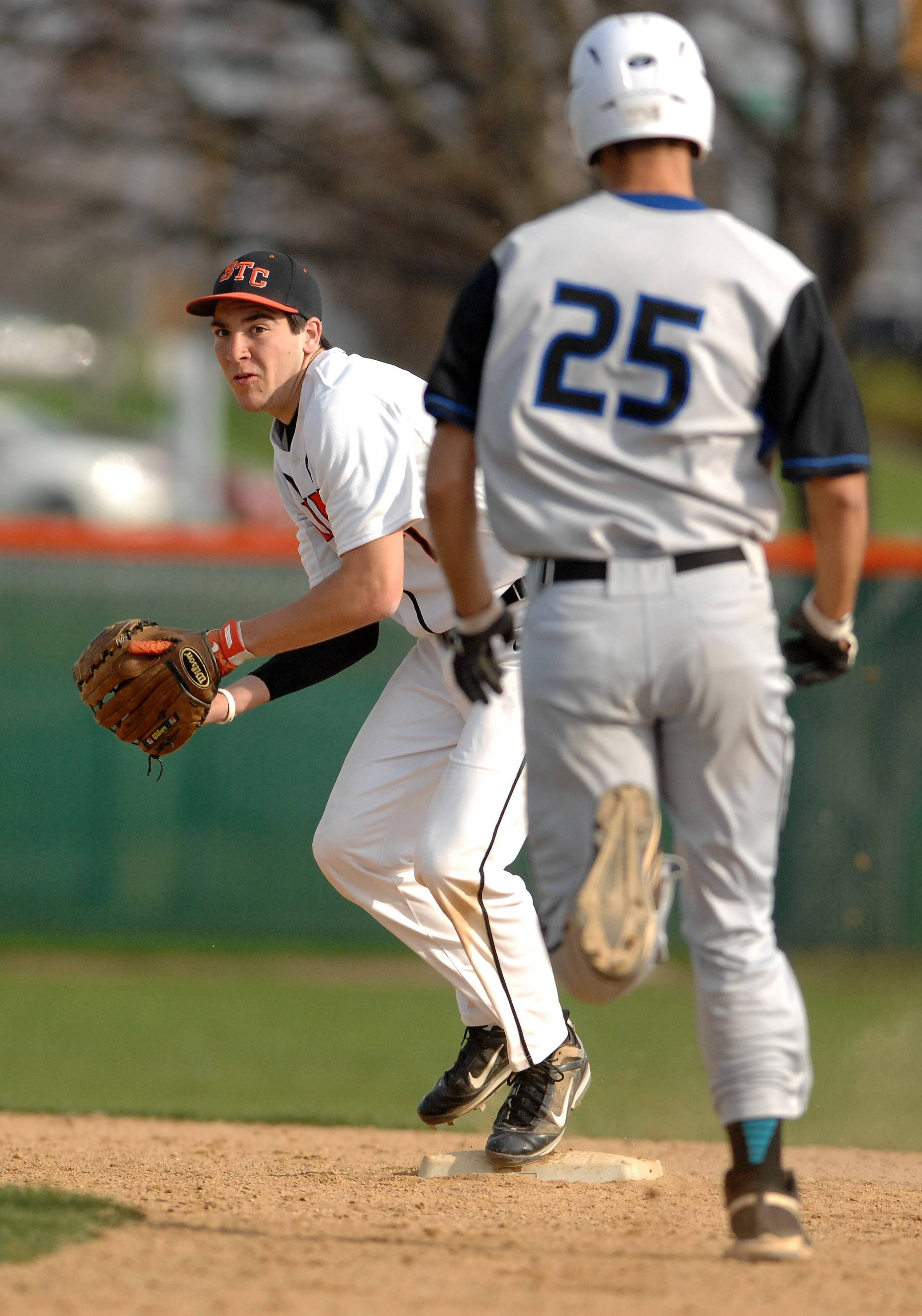 St. Charles East's Jake Asquini (7) takes the throw and looks to turn a double play as St. Charles North's Joe Kuczek (25) bears down during Tuesday's game at St. Charles East.