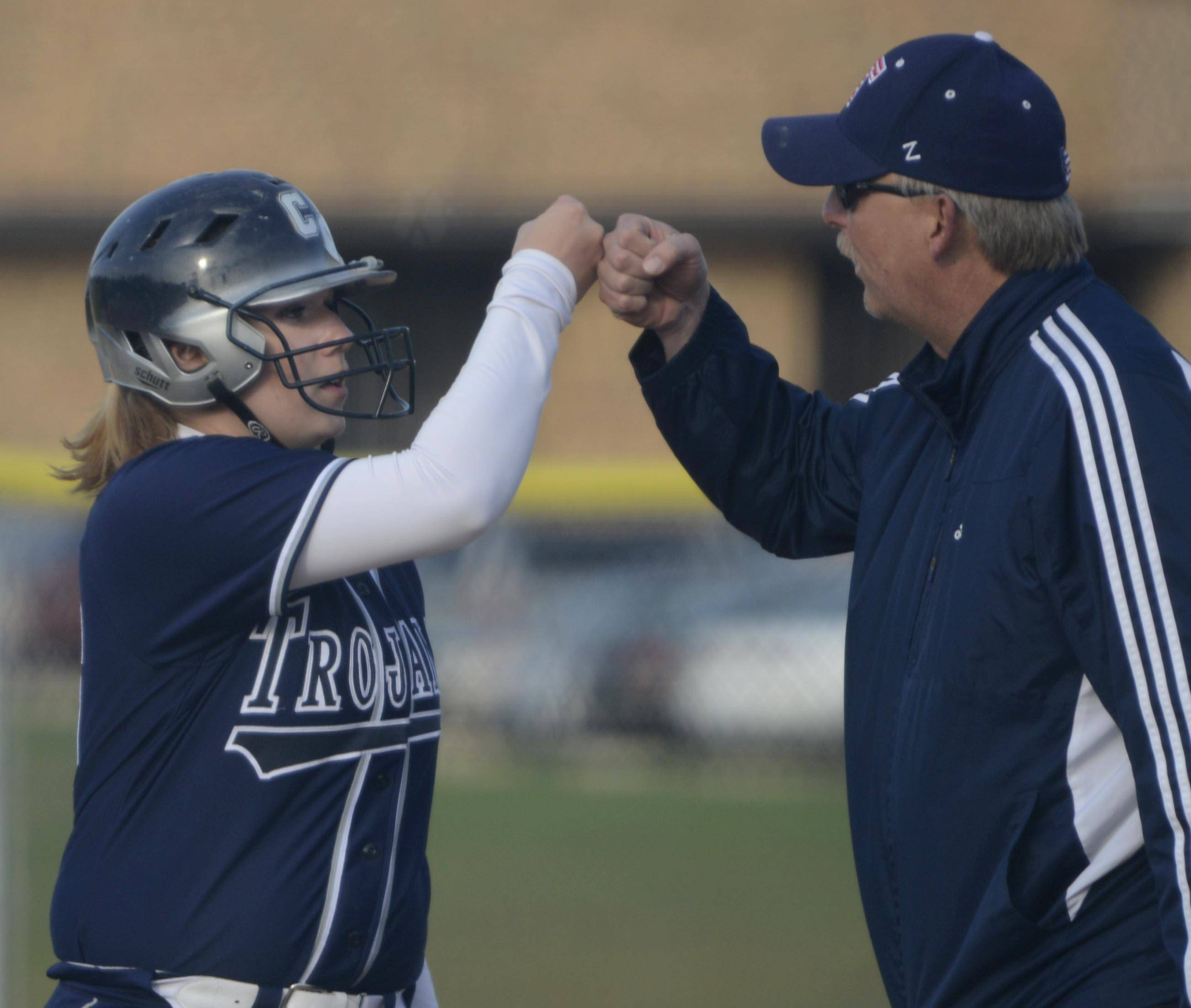 Cary-Grove's Amanda DeGroote is congratulated on her 2-RBI basehit against Jacobs in the fifth inning by assistant coach Mark Olson Tuesday in Cary.