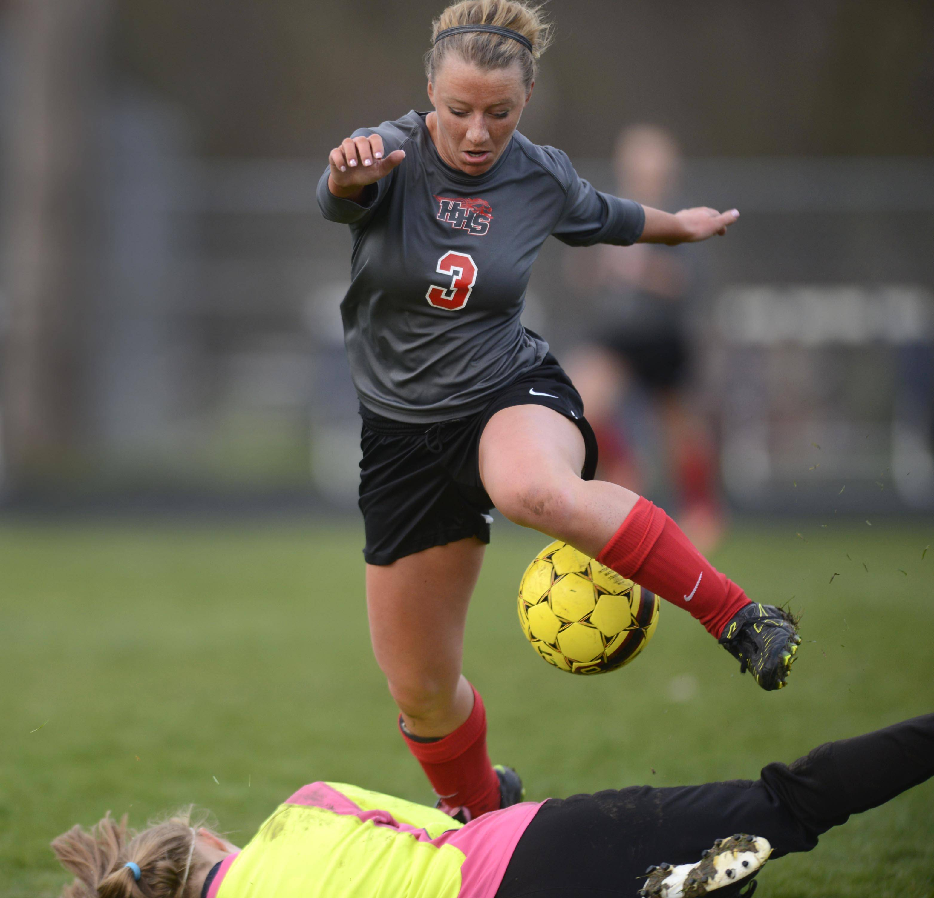 Cary-Grove goalkeeper Morgan Olsen slides under Huntley's Jessica Helm as she charges the net Thursday in Cary.
