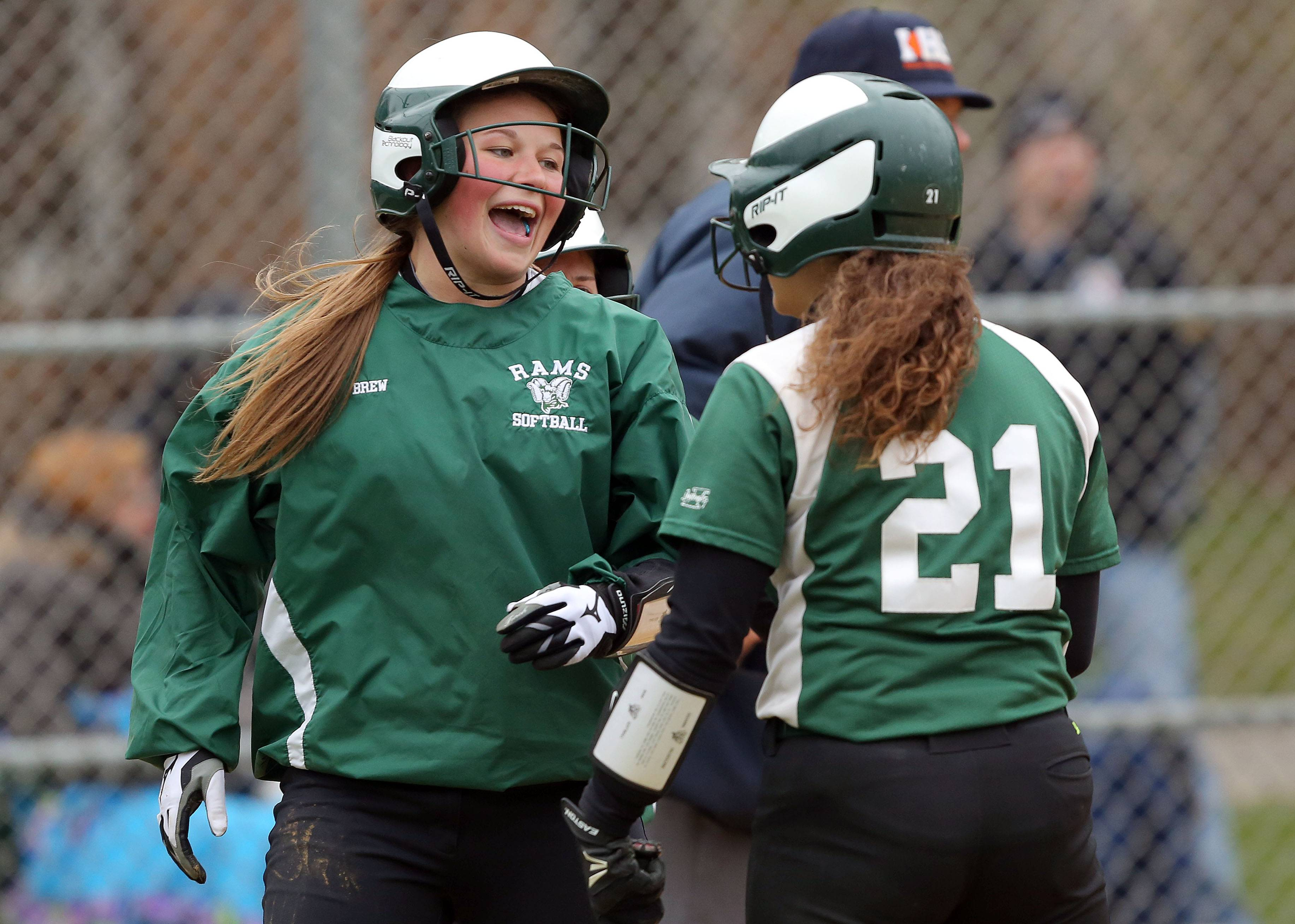 Grayslake Central's Jamie Brew, left, celebrates with Juliana Frusolone after scoring during Monday's softball game against Grayslake North.