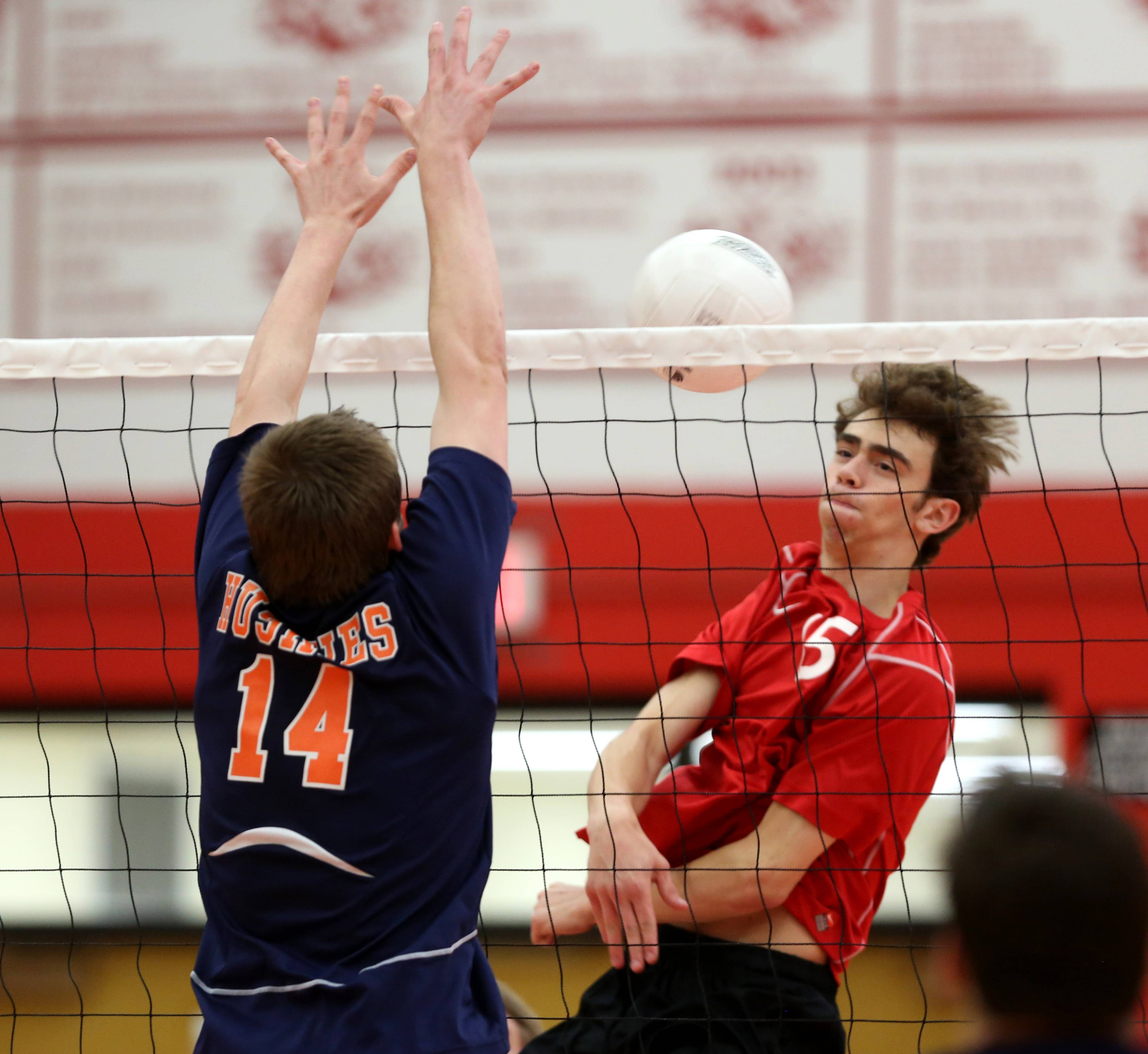 Naperville North's Frank Dore, left, battles Naperville Central's Tanner Beck, right, during Tuesday's volleyball match.