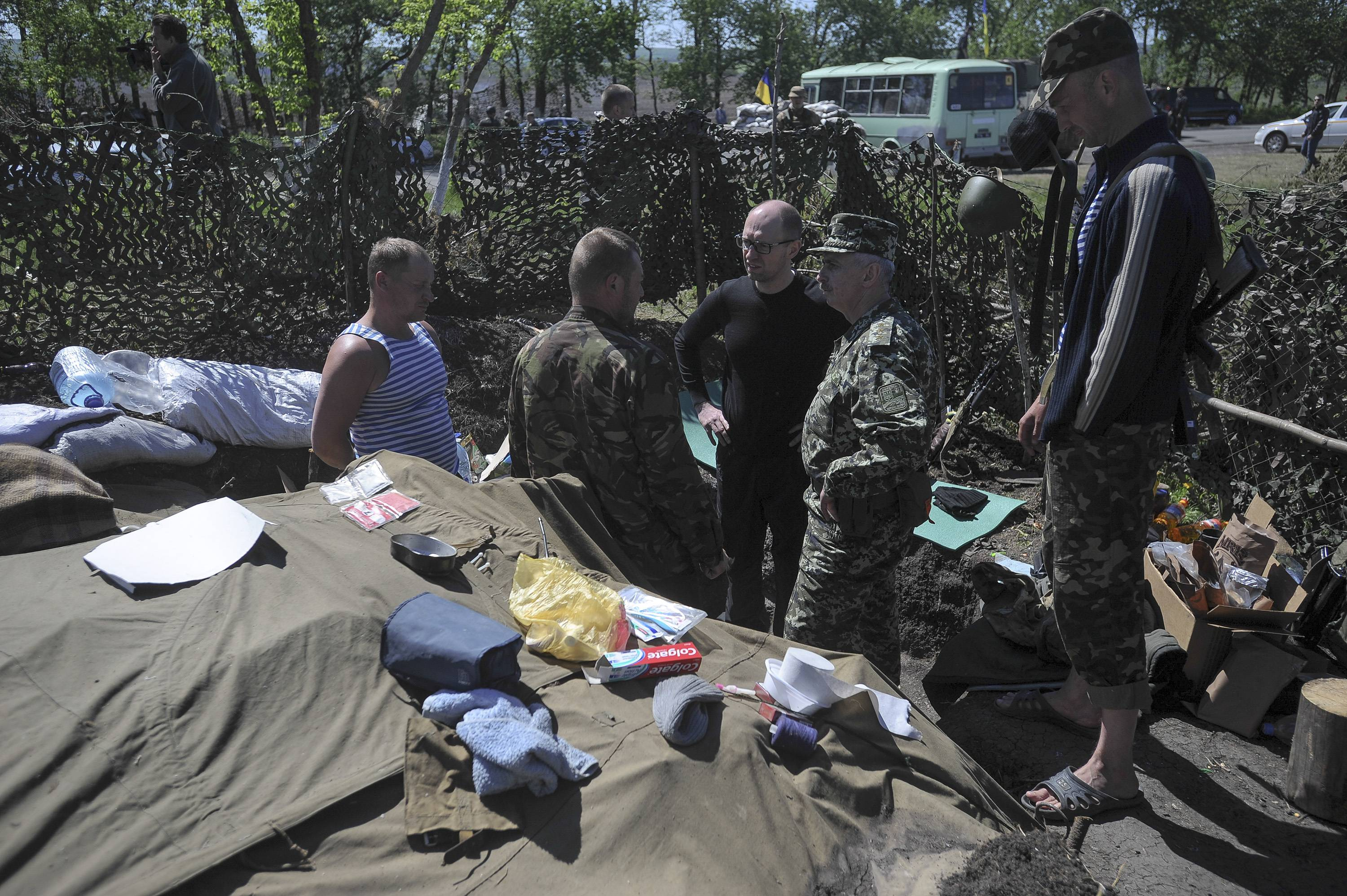 Ukrainian Prime Minister Arseniy Yatsenyuk, center, talks with Ukrainian soldiers Wednesday. Russian President Putin announced Russia has pulled back its troops from the Ukrainian border.
