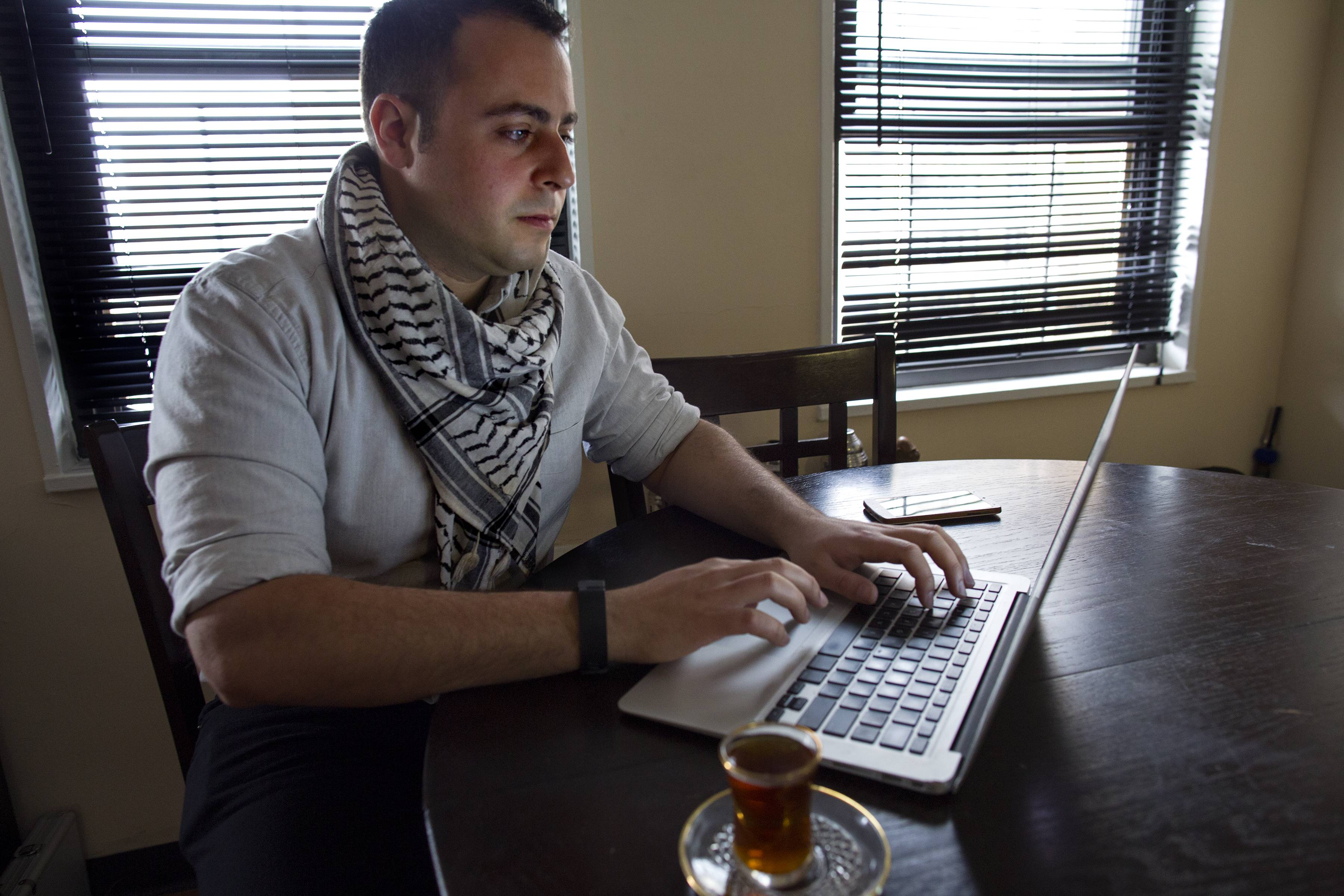 Bashar Makhay answers messages on a computer in his apartment in the Brooklyn borough of New York. Makhay, who is Iraqi-American, Catholic and gay, said he has created Tarab, a series of parties, beach gatherings and other events for LGBT Arabs and Middle Easterners in New York City.