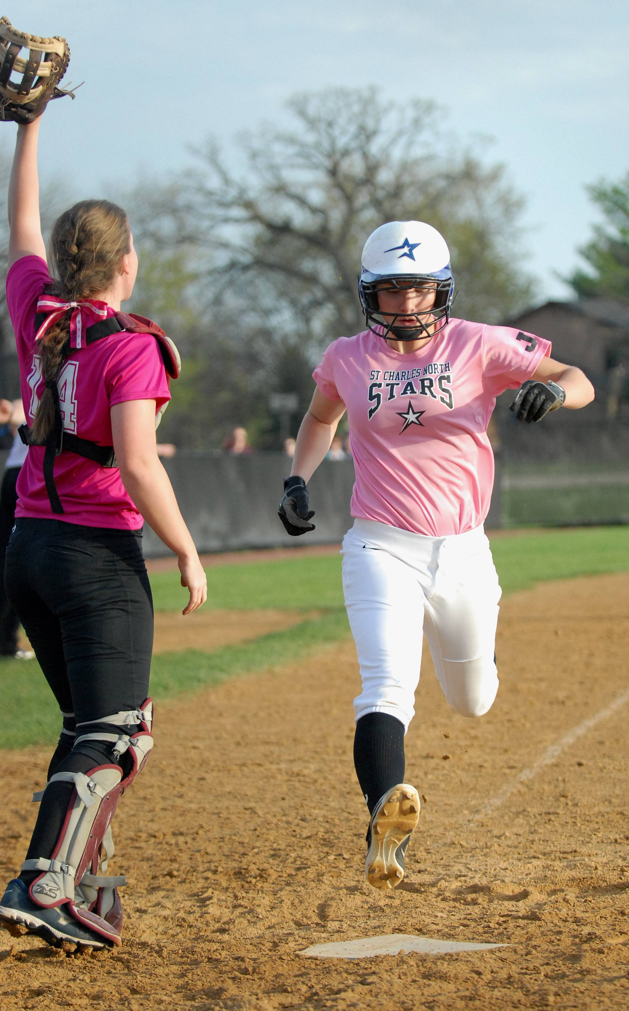 St. Charles North's Andrea Beal strides over home plate past Geneva catcher Kaitlyn Plocinski, bringing in a run for the North Stars in the fourth inning on Wednesday, May 7.