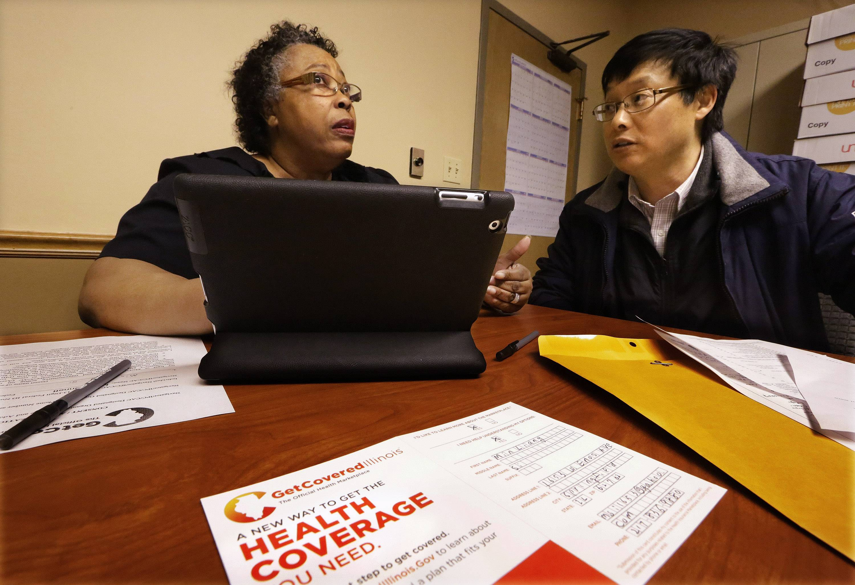 Mary Bennett, left, helps Min Lians, who is seeking help buying health insurance under the Affordable Care Act at the Family Guidance Center in Springfield.
