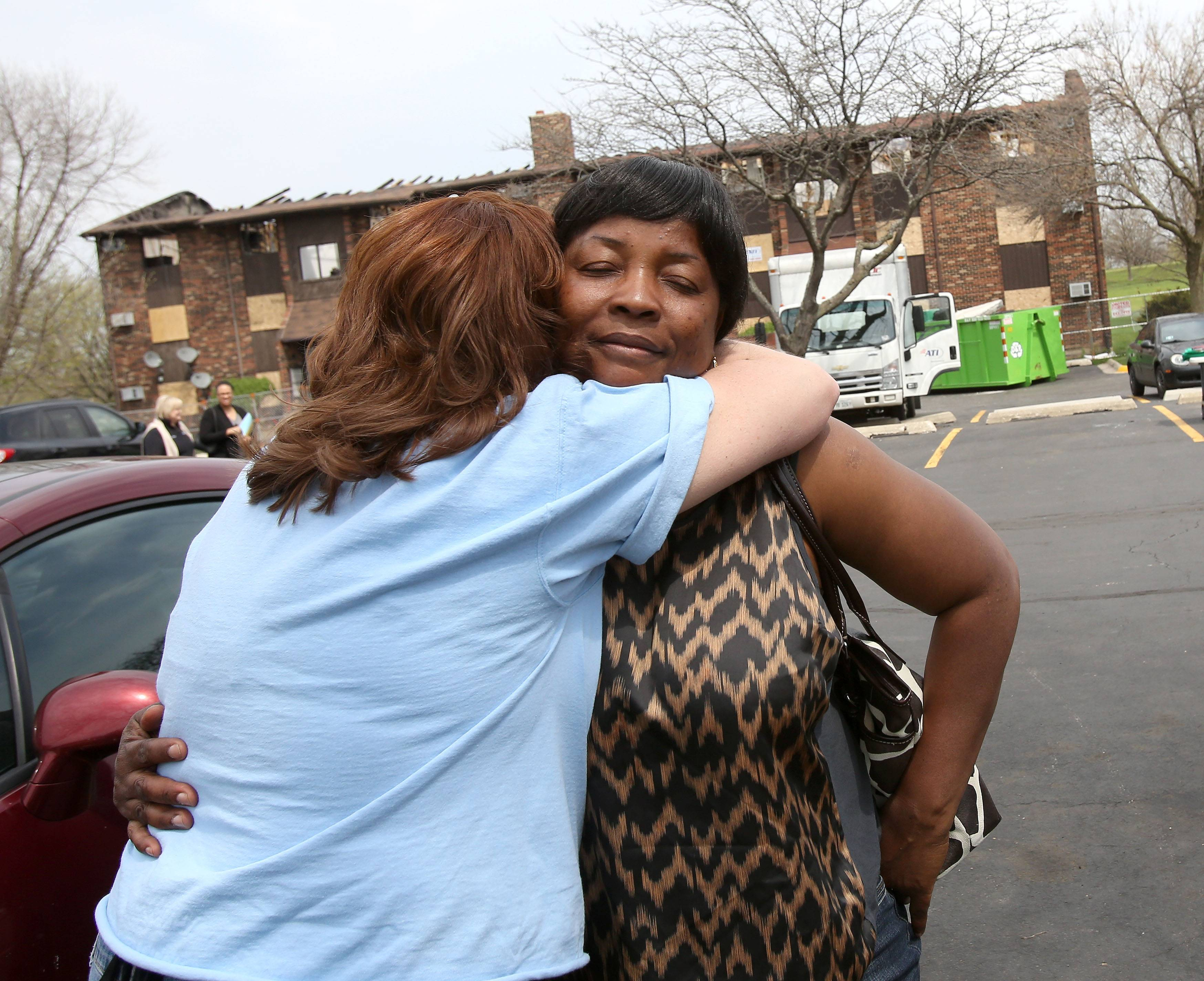 Ruthstar Owusu gets a hug from Debbi White, left, of the Woodridge Jaycees. Eleven families, including Owusu's,   were left homeless after a May 1 apartment fire in Woodridge. Several community groups were on hand Wednesday to provide food, clothing and financial assistance.