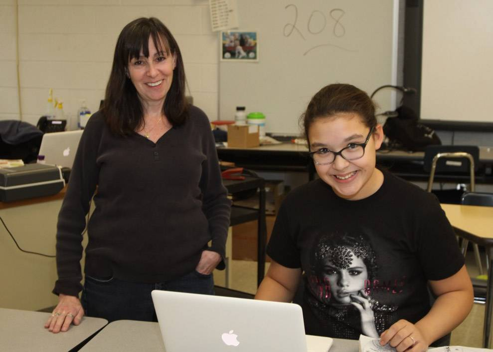Nancy Braun, a Mundelein Elementary District 75 technology assistant, and eighth-grader Juliana Roznowski work on a laptop computer at Carl Sandburg Middle School. The district plans to make a substantial investment this summer in technology for students.