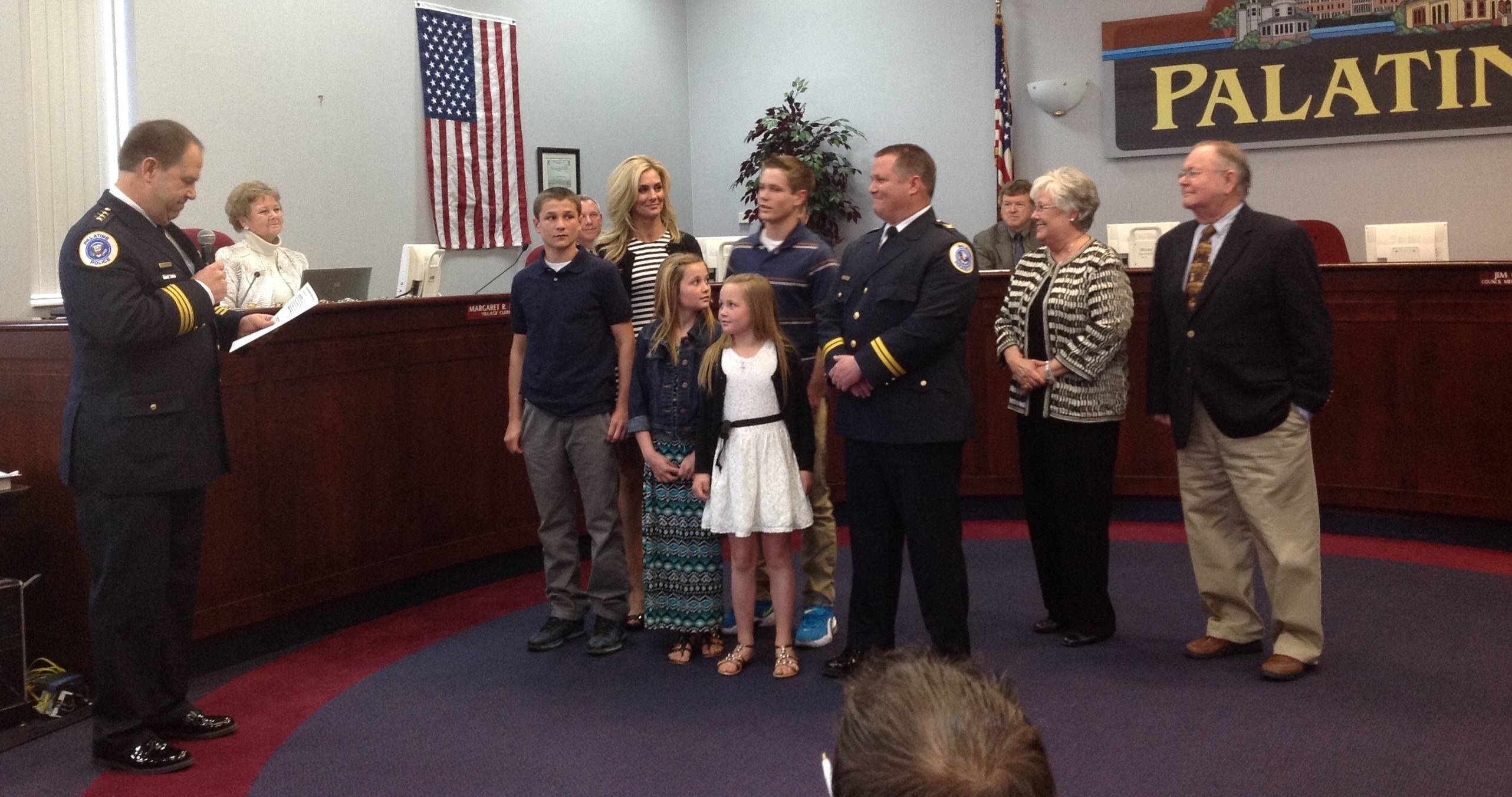 Palatine Police Chief Alan Stoeckel, left, pauses while speaking about Dave Daigle, center, who was promoted to deputy chief of field operations in a ceremony during the Palatine village council's meeting Monday night. Daigle is surrounded by his wife, Maria Daigle, left, his parents, Carol and David Daigle, and his four children.