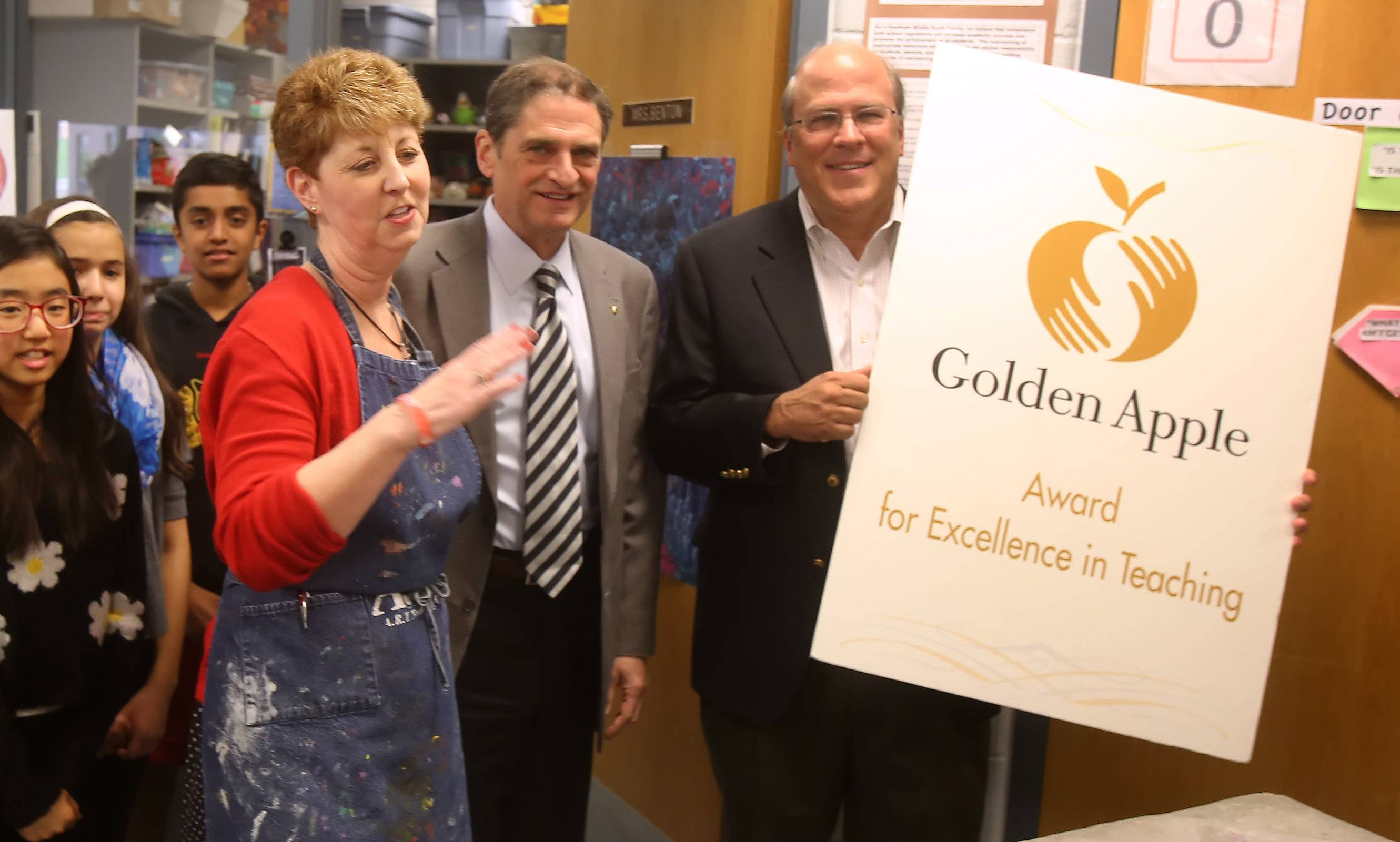 Golden Apple representatives Greg Salustro, left, and Franklin Morton present the Golden Apple Award for Excellence in Teaching to Hawthorn Middle School art teacher Mary Benton in her classroom Wednesday morning.