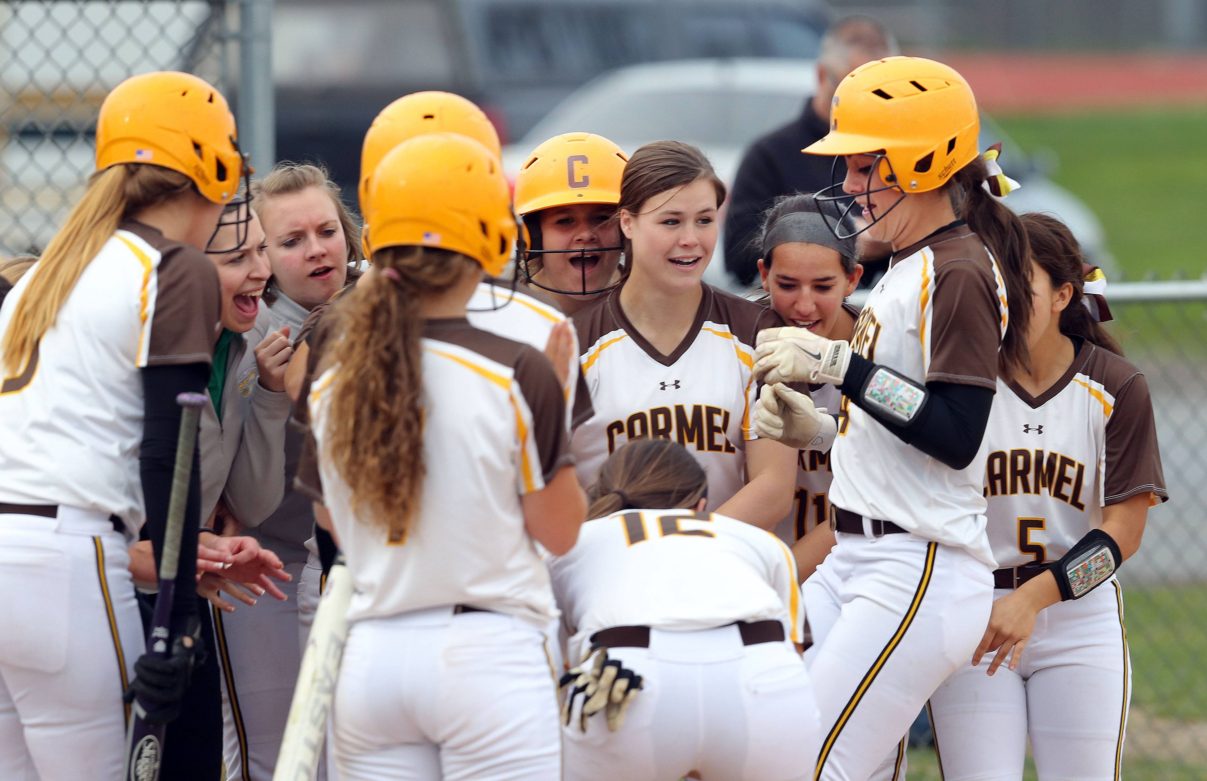Carmel's Kathleen Felicelli, right, is greeted by teammates after connecting for a 3-run homer against Nazareth on Wednesday in Mundelein.