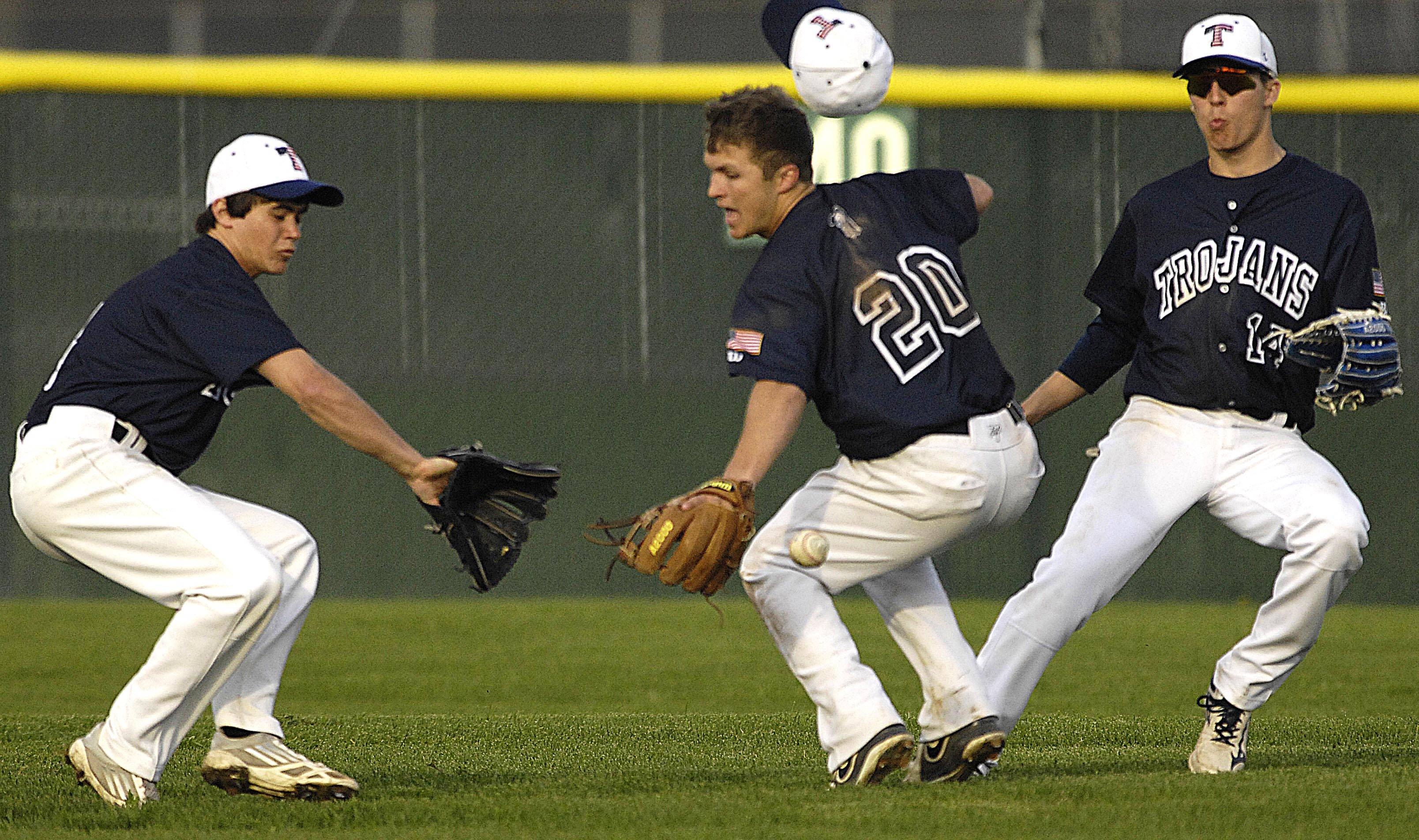 Cary-Grove's Larkin Hanselmann, left, Matt Sutherland, and Jim Perkins converge on a pop up that dropped in short center field off the bat of Dundee-Crown's Brett Johnson in the sixth inning Wednesday in Cary.