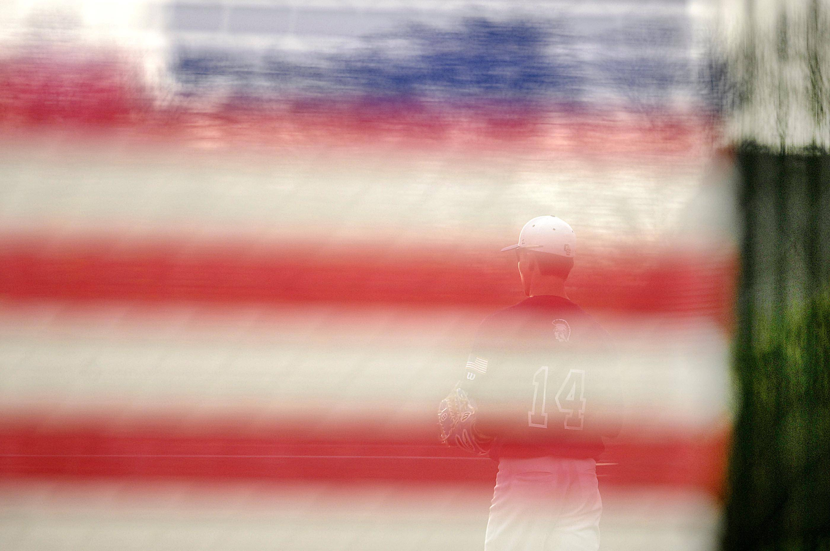 Cary-Grove right fielder Jim Perkins can be seen behind an American flag designed into the outfield fence Wednesday in Cary.