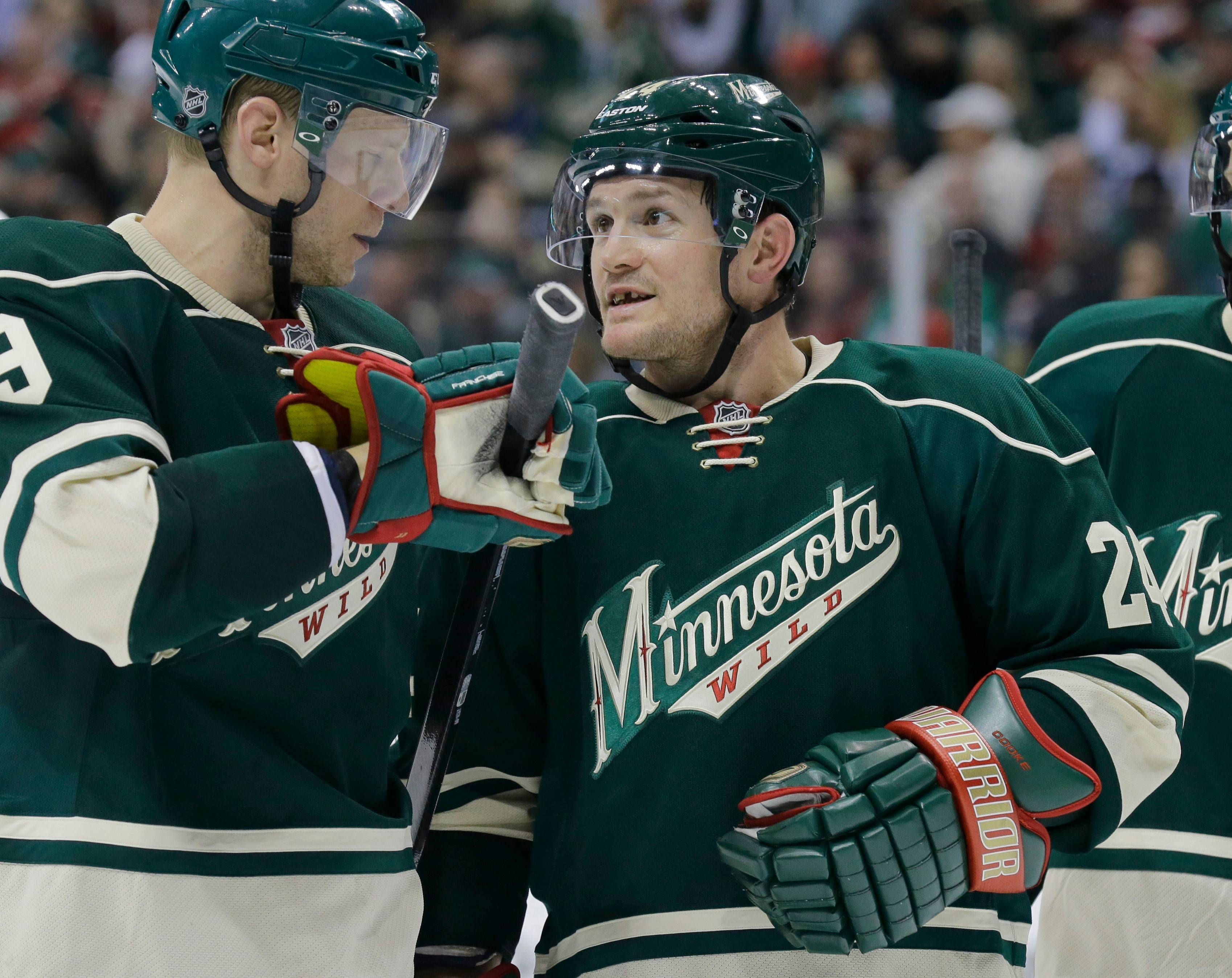 Wild forward Matt Cooke, at right talking to teammate Mikko Koivu, will be back for Game 4 against the Hawks after serving a seven-game suspension for a hit he delivered to Colorado's Tyson Barrie in the first round.