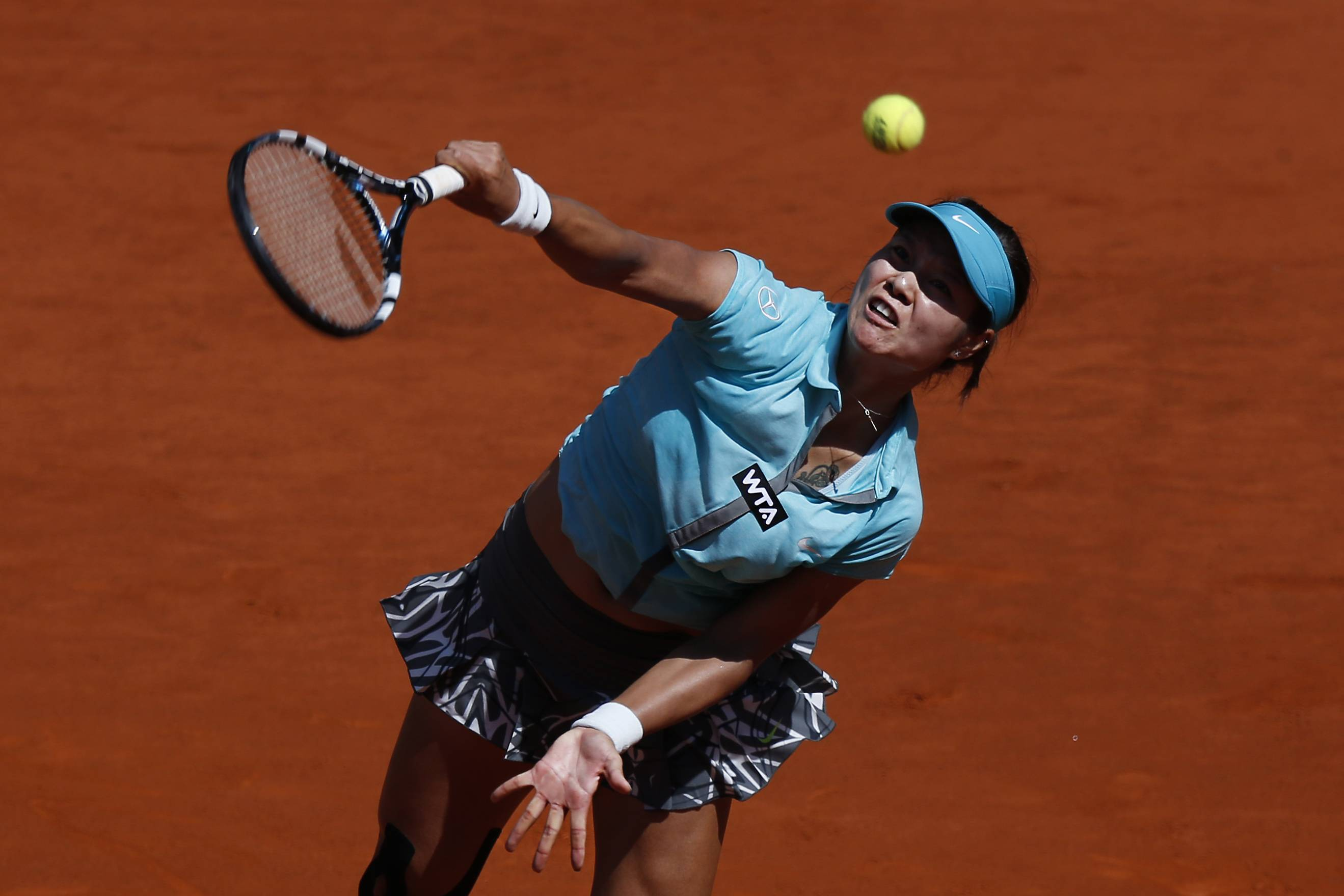 Na Li from China serves the ball during a Madrid Open tennis tournament match against Sloane Stephens from the U.S. in Madrid, Spain, Thursday, May 8, 2014.