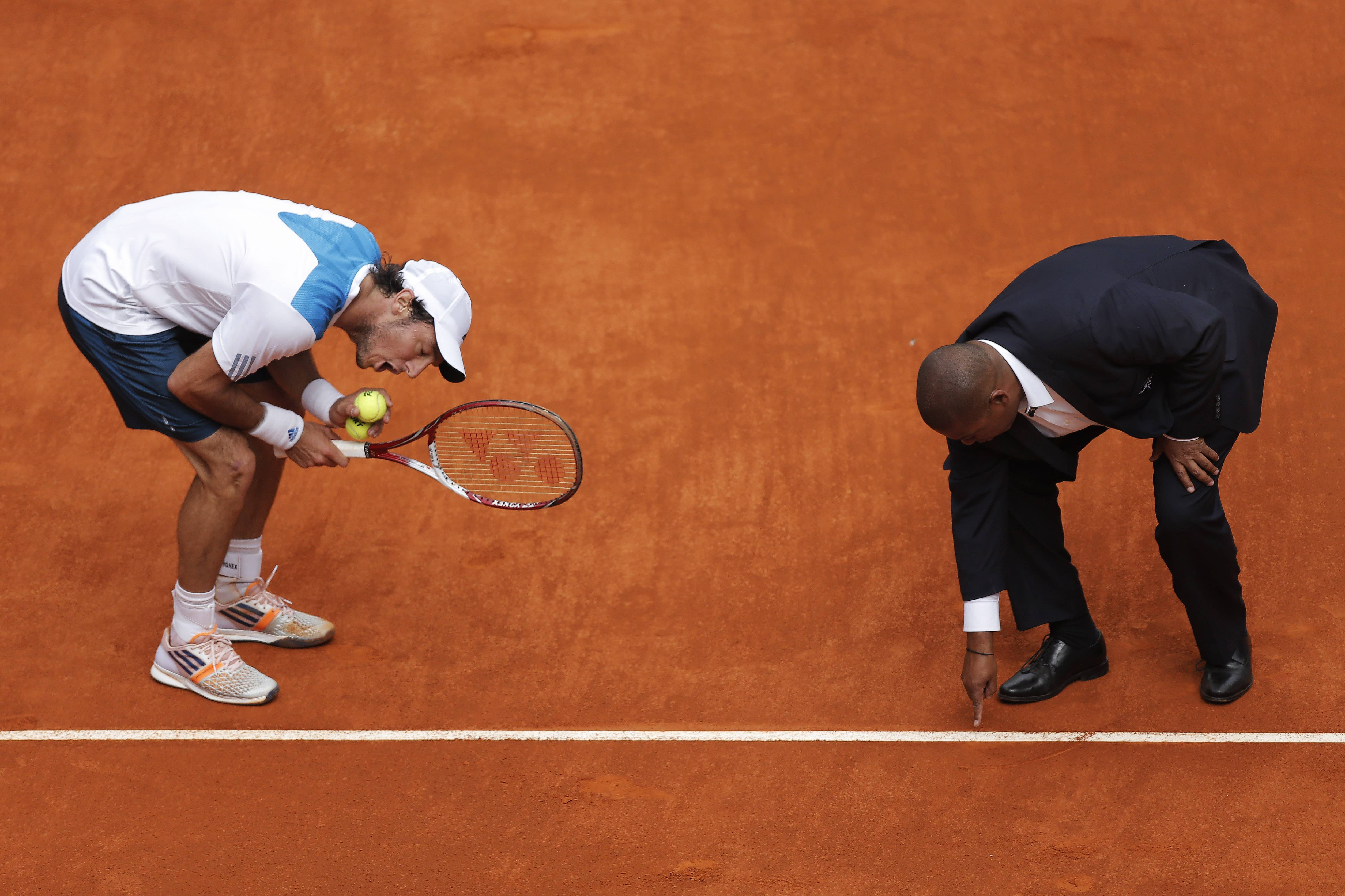 Juan Monaco from Argentina, left, discusses a point with umpire Carlos Bernardes during a Madrid Open tennis tournament match against Rafael Nadal from Spain in Madrid, Spain, Wednesday, May 7, 2014. (AP
