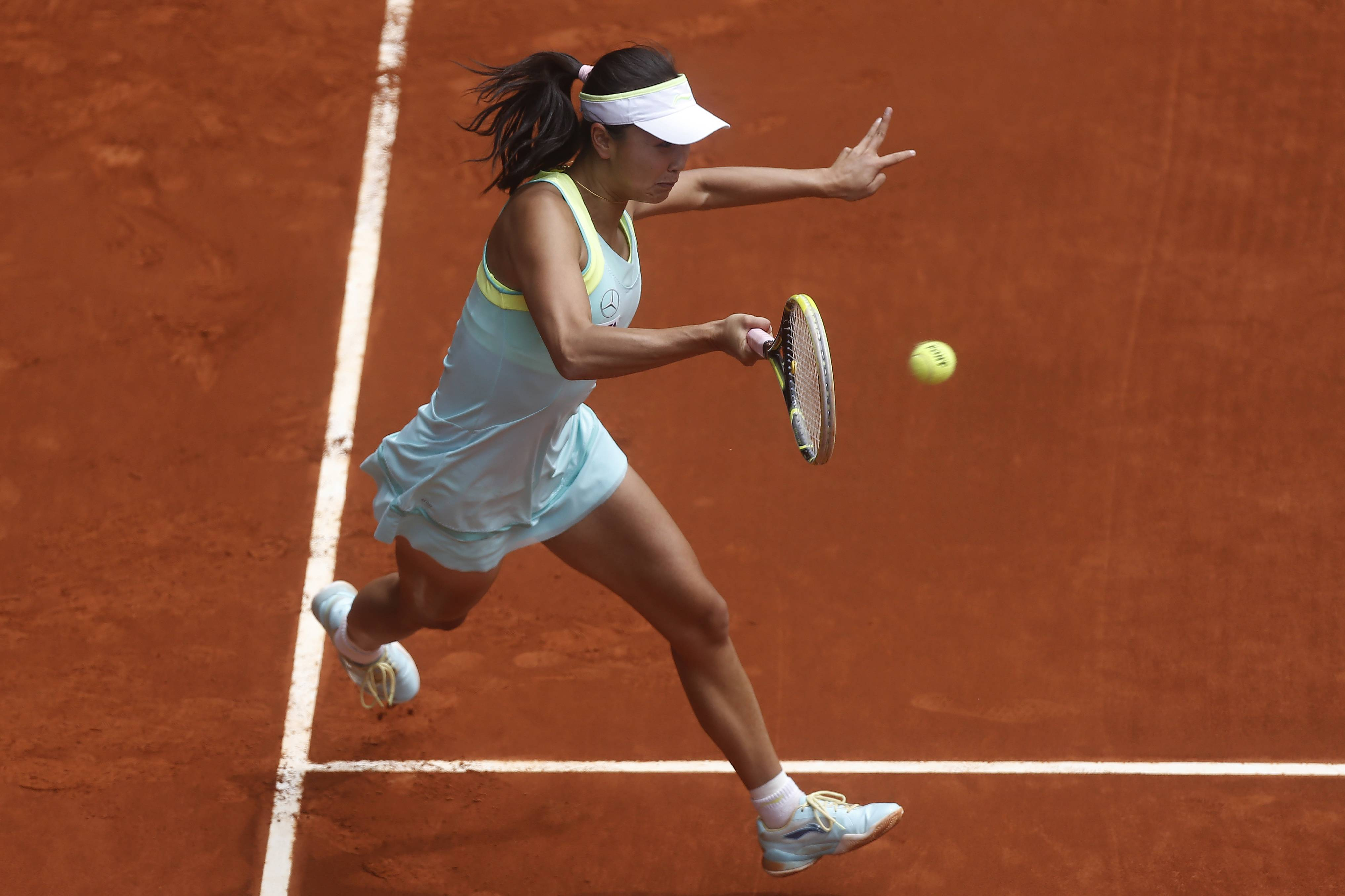 Shuai Peng from China returns the ball during a Madrid Open tennis tournament match against Serena Williams from U.S., in Madrid, Spain, Wednesday, May 7, 2014.