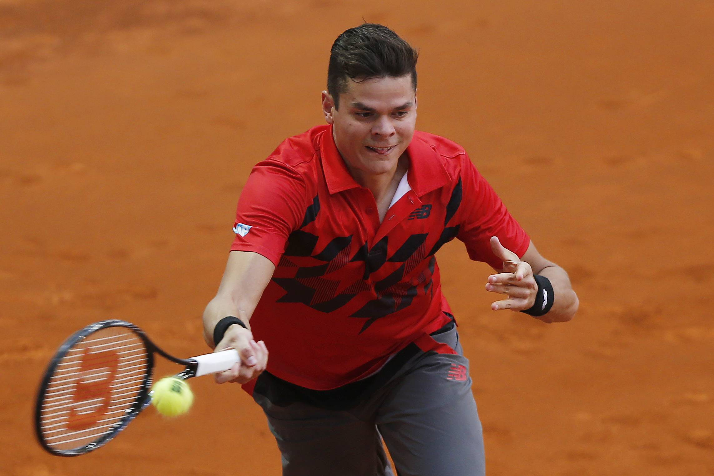 Milos Raonic from Canada returns the ball during a Madrid Open tennis tournament match against Jeremy Chardy from France, in Madrid, Spain, Tuesday, May 6, 2014.