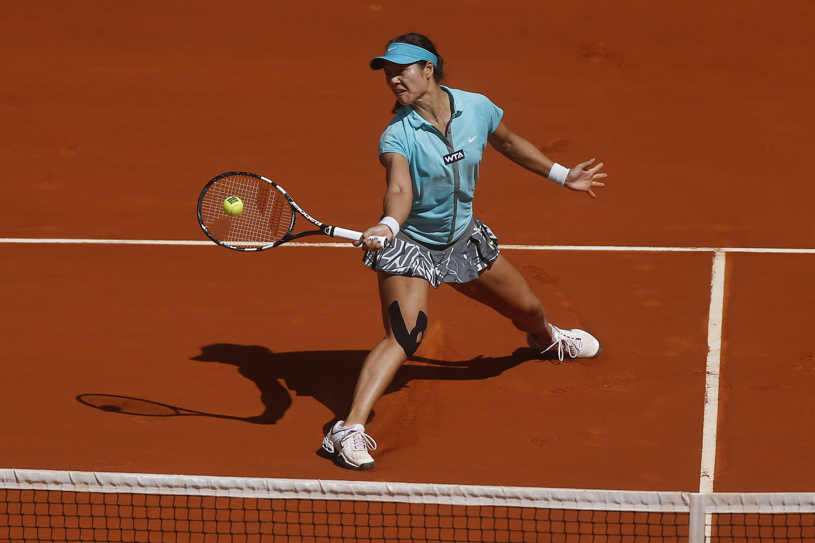 Li Na from China returns the ball during a Madrid Open tennis tournament match against Jie Zheng from China, in Madrid, Spain, Tuesday, May 6, 2014.